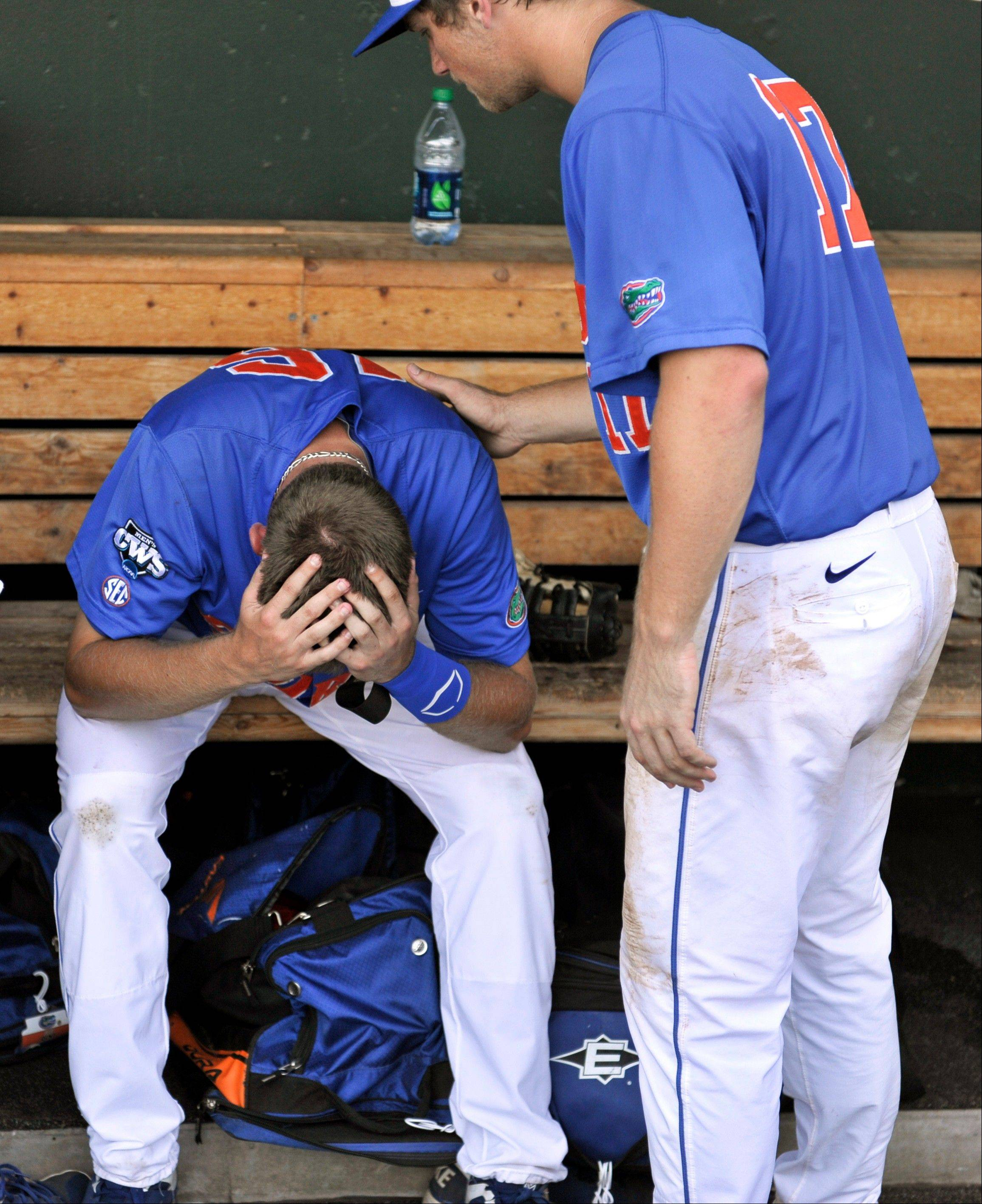 Florida's Taylor Gushue consoles teammate Justin Shafer, left, after they lost 5-4 to Kent State in an NCAA College World Series elimination game Monday in Omaha, Neb.