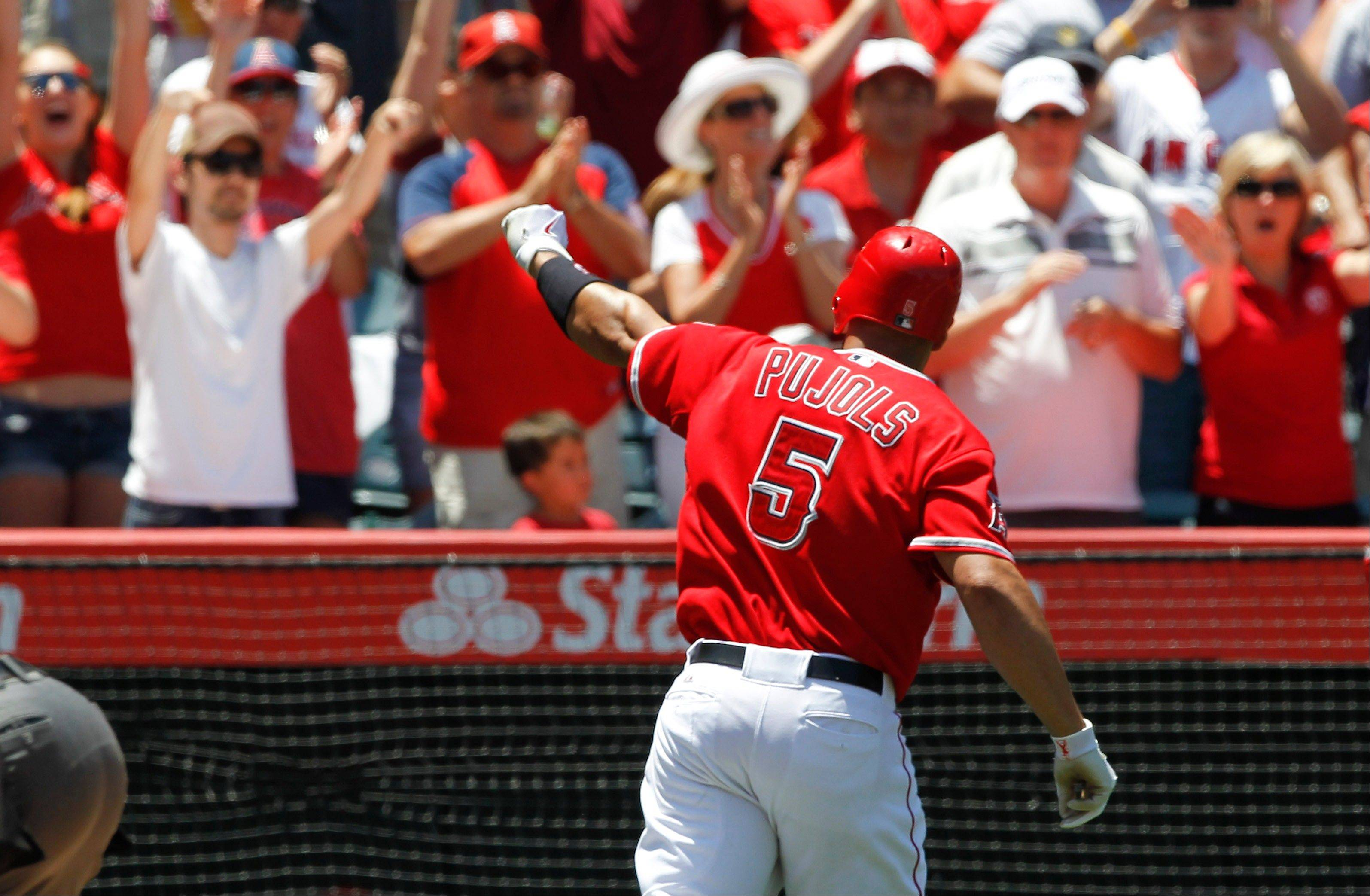 "Albert Pujols celebrates with fans after hitting a home run Sunday for the Los Angeles Angels. Twelves years ago, Pujols was playing in the Midwest League All-Star Game and deemed ""someone to watch."" A new crop of all-stars will be in Geneva tonight for the annual classic. The Cougars organization has planned a Chicago theme to the event, complete with Wayne Messmer and Nancy Faust joining in."