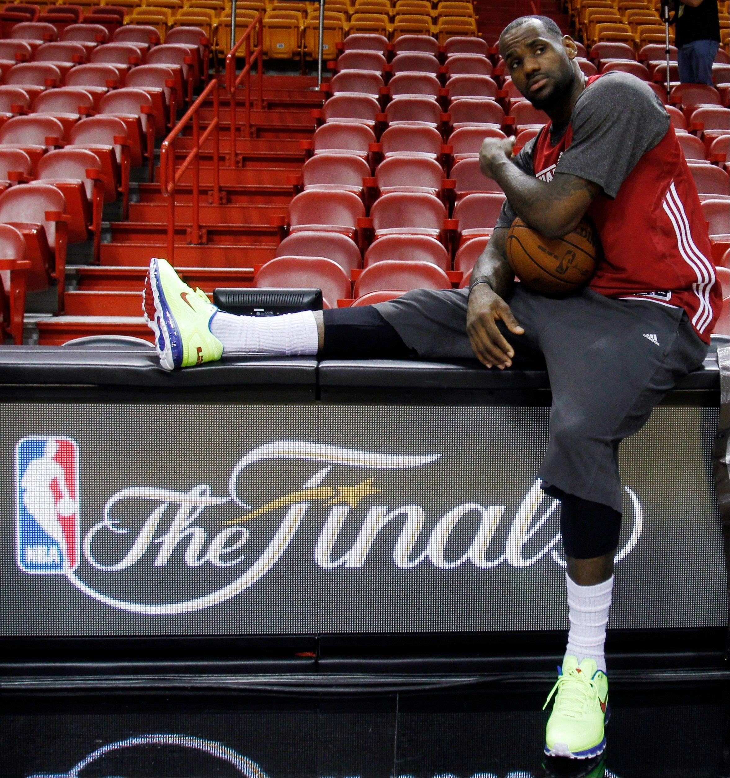 Miami Heat small forward LeBron James takes a break on the scorer's table during practice Monday in Miami. The Heat play the Oklahoma City Thunder in Game 4 of the NBA basketball finals on Tuesday.