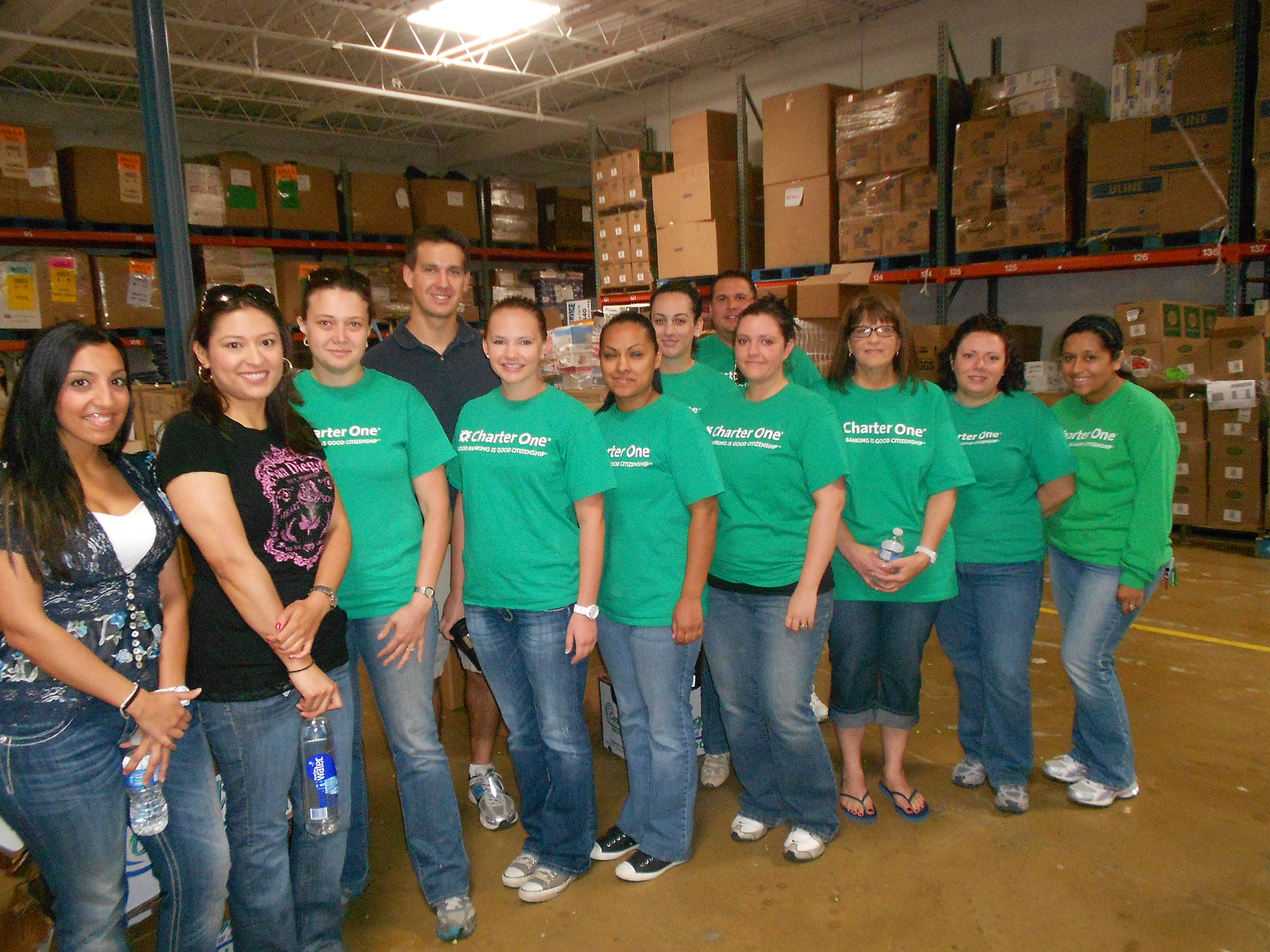 Charter One volunteers, in HSP's warehouse, excited to help with the Feed The Kids Project.