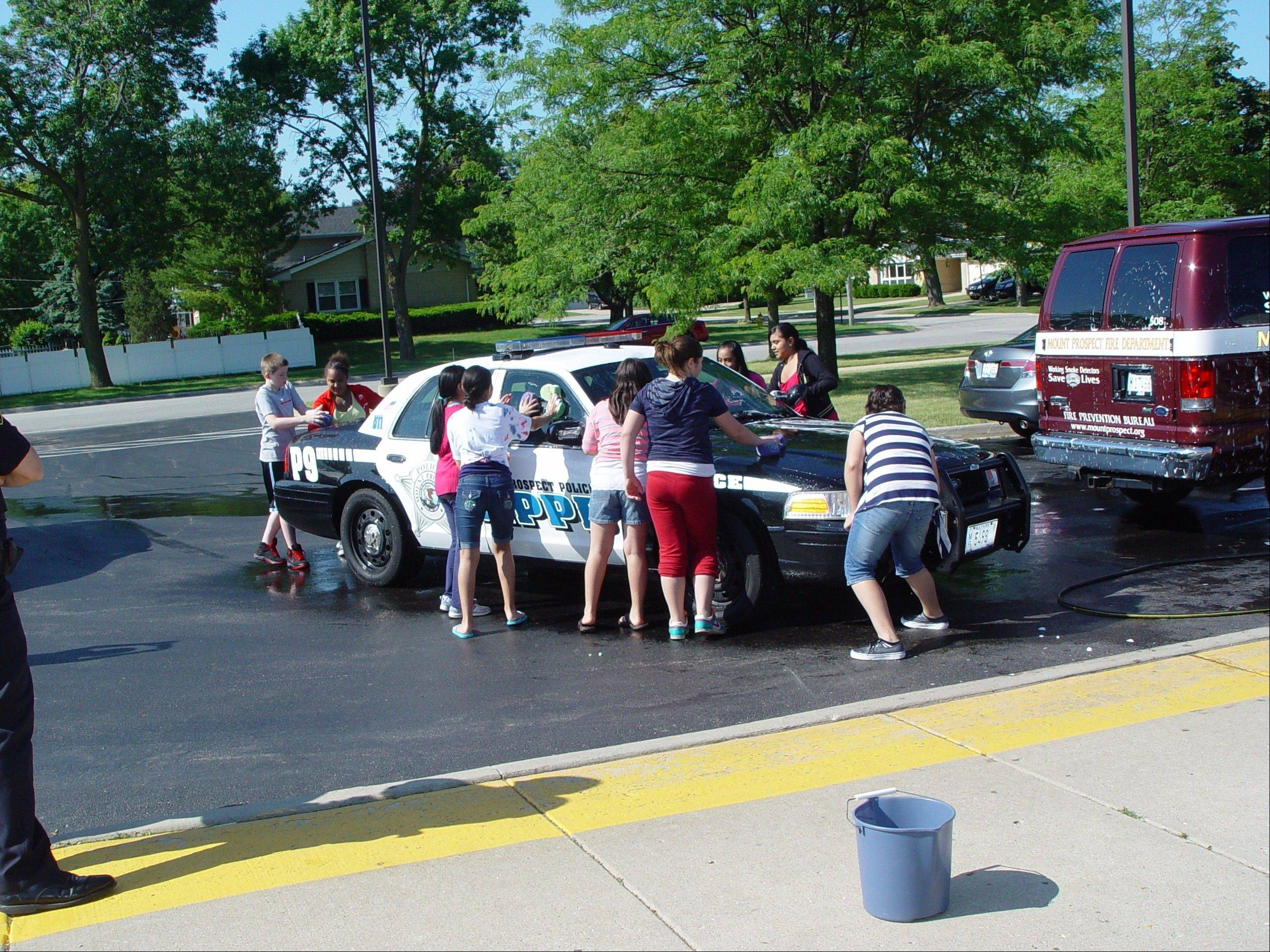 Holmes Junior High students wash a Mount Prospect police vehicle during a free community car wash, as part of their many day of service activities.