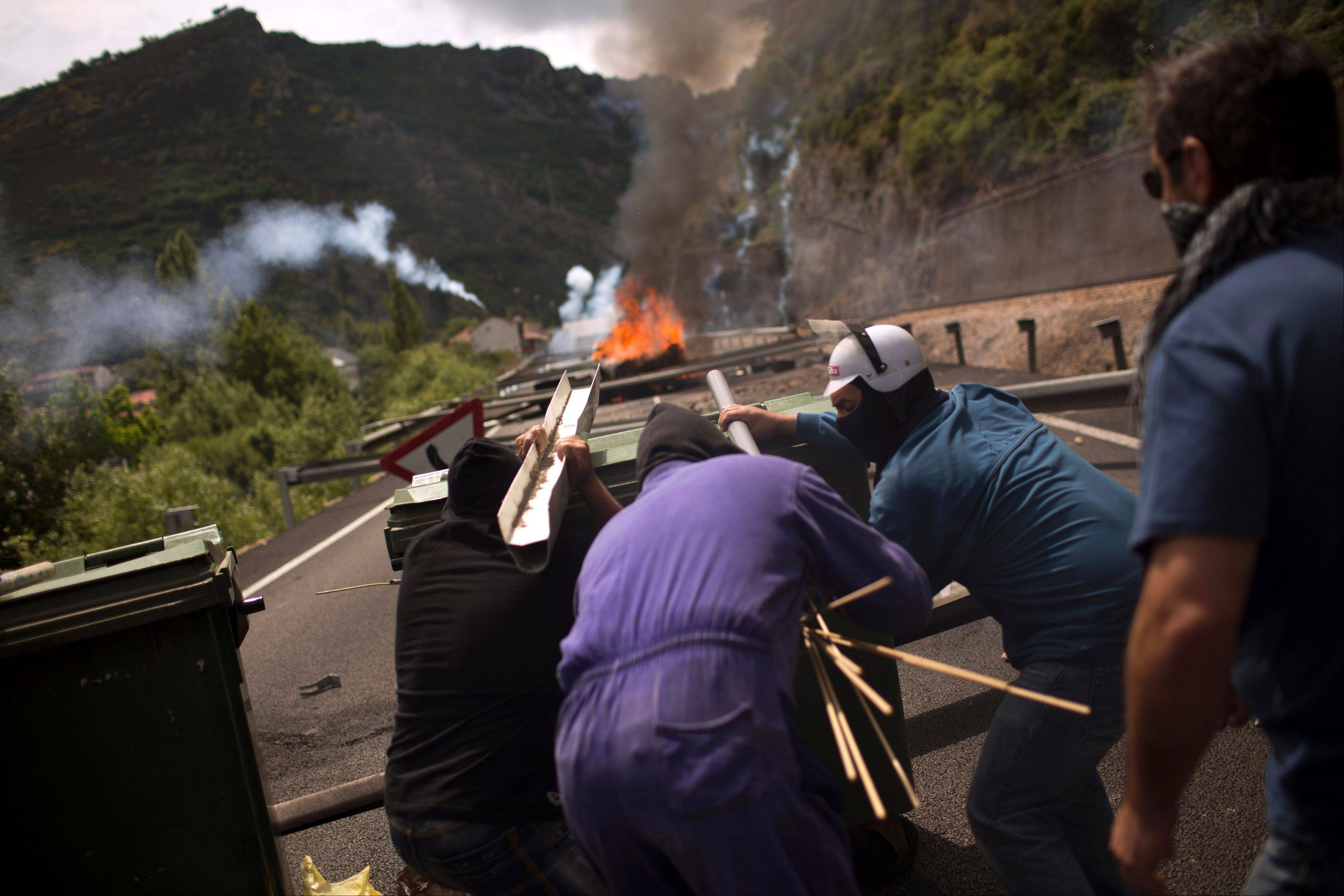 Miners fire handmade rockets at riot police as they defend their position after blocking a road Tuesday in Cinera, near Leon, Spain.