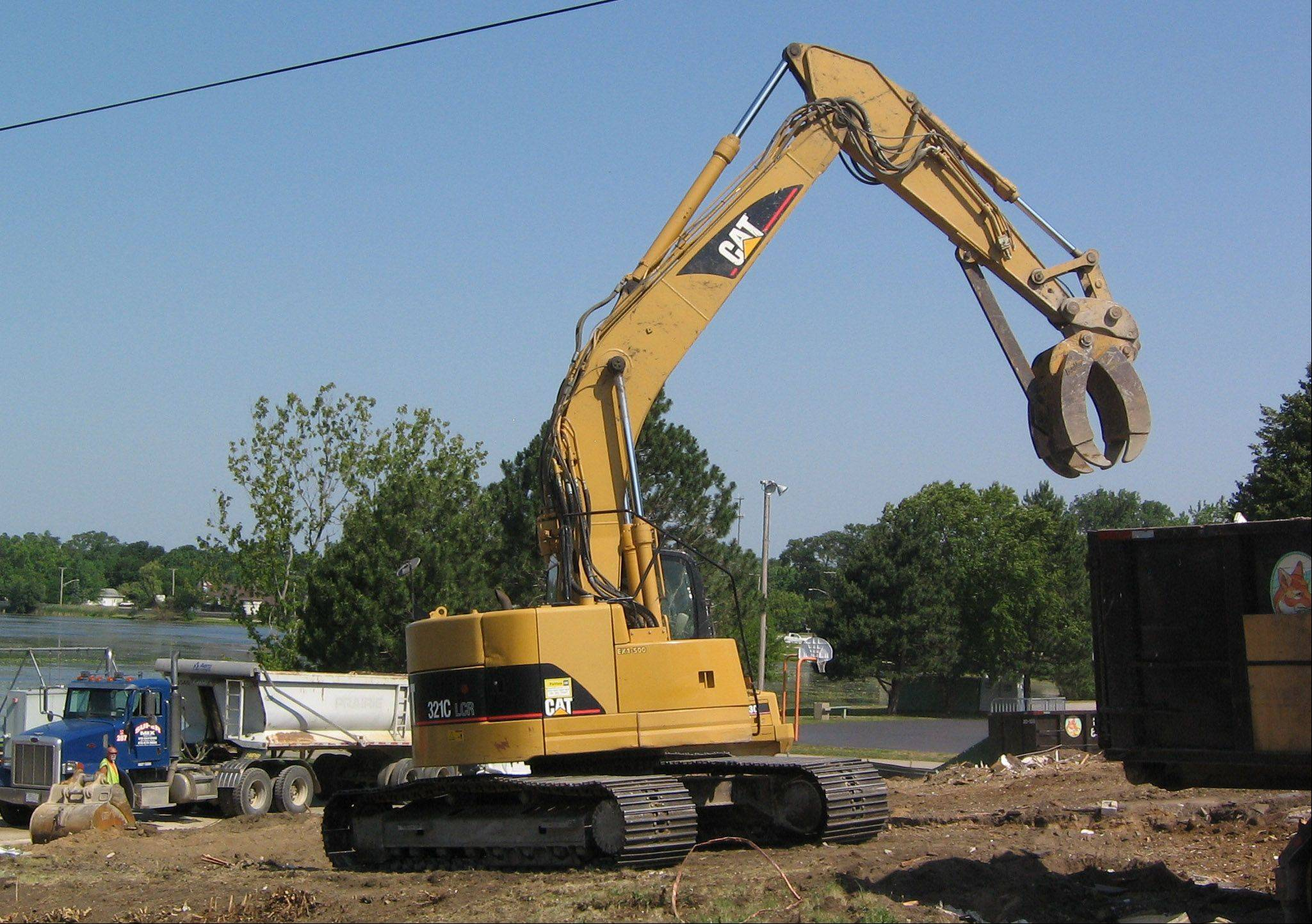 The remains of two homes fronting Lily Lake are cleared Tuesday as part of a bigger plan for Morrison Park in Lakemoor.