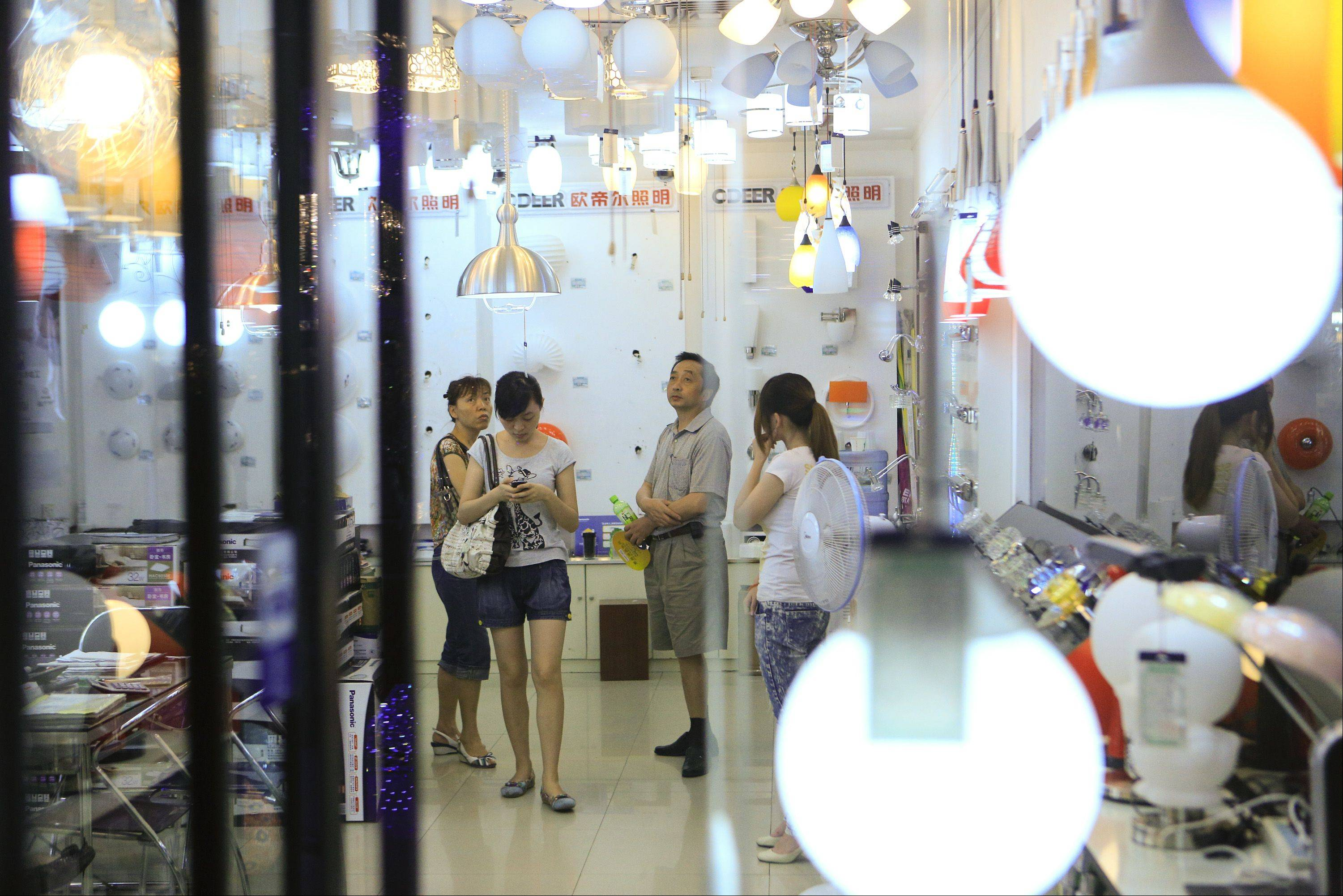 Customers shop for lighting at a home furnishing store Tuesday in Beijing, China. China's economy, the world's second biggest, is producing more millionaires.