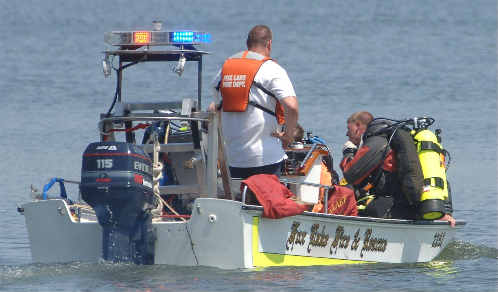 Boats carrying divers head to the search area to look for a missing swimmer on Gages Lake Tuesday near Grayslake.