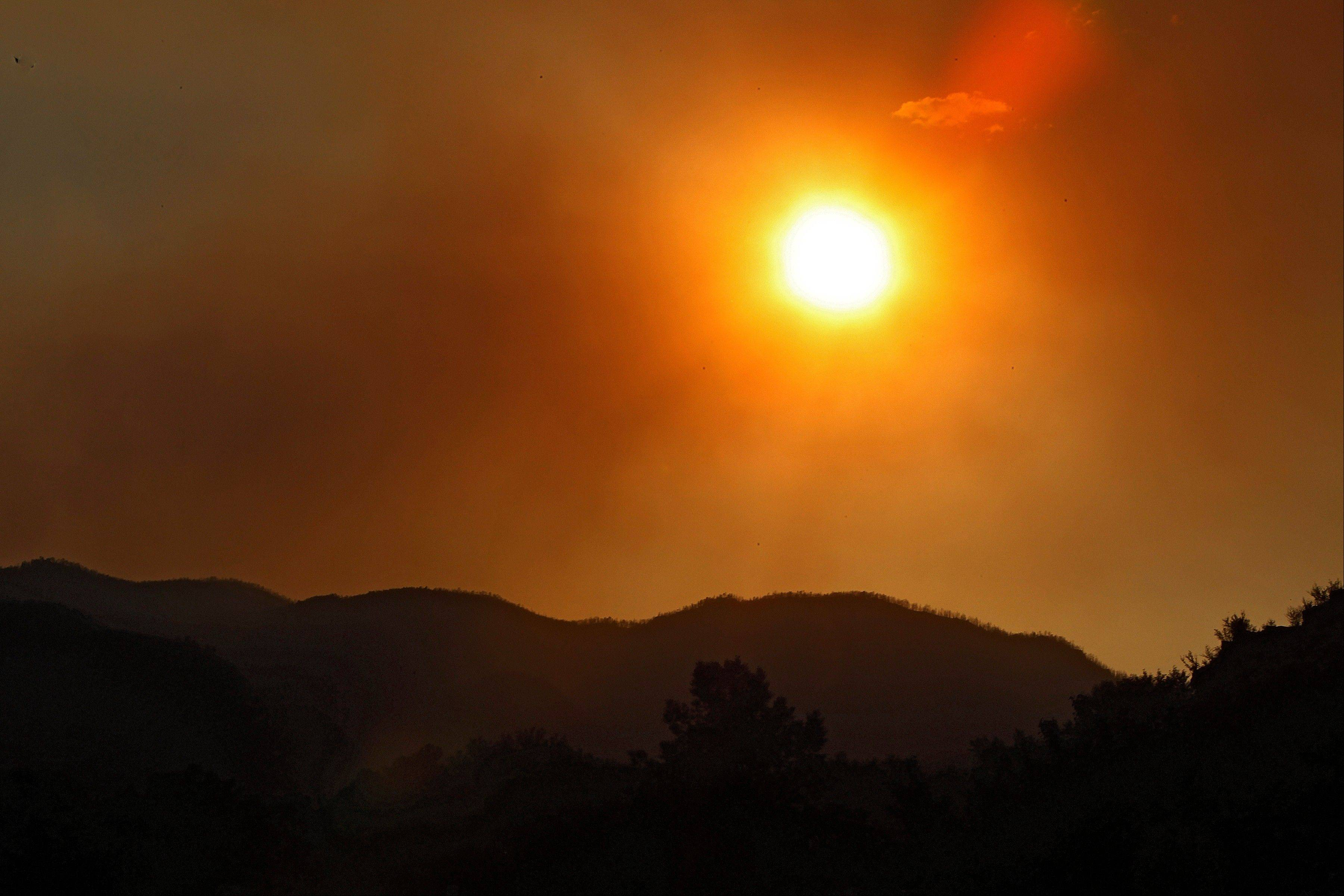 The sun sets amidst smoke from the High Park Fire near Bellvue, Colo., on Monday, June 18, 2012. The wildfire has now burned about 90 square miles and destroyed more than 180 homes.