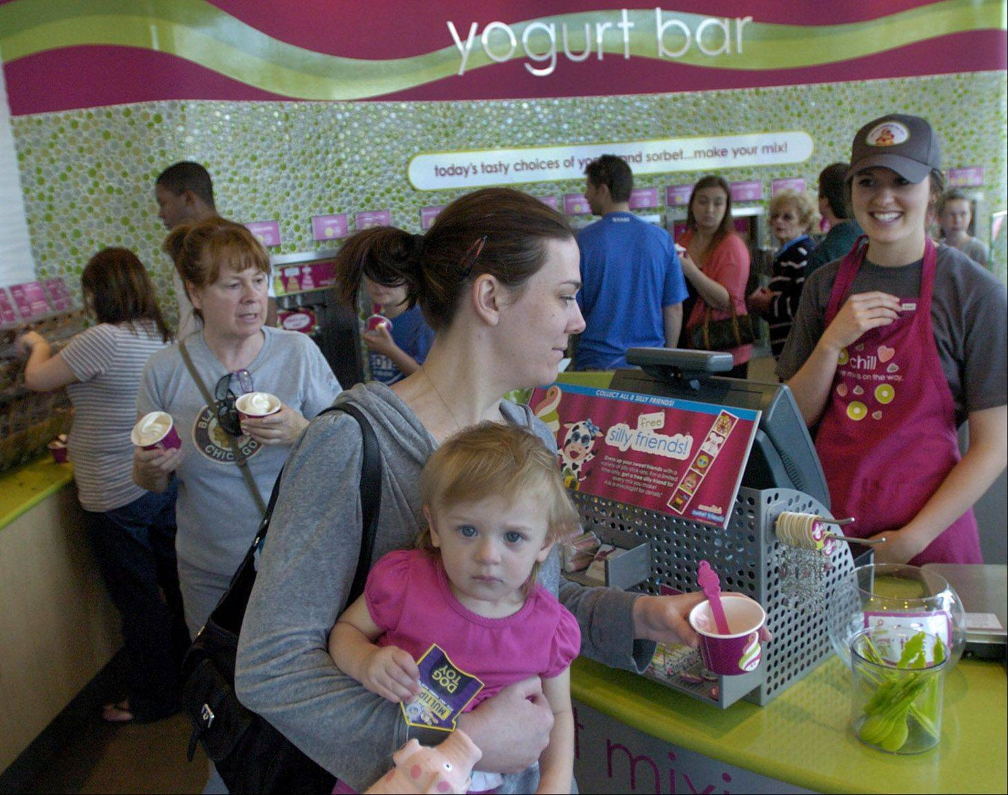 Tiffany Black makes her way through the yogurt line with 17-month-old Liliana Louis at the new Menchie's frozen yogurt in Mount Prospect.