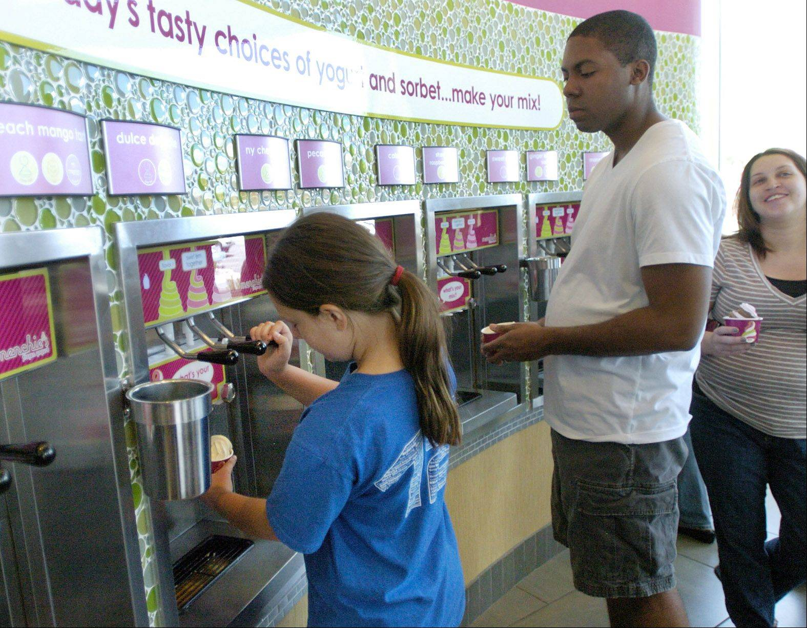 Maggie Haselet helps herself to some free frozen yogurt during the grand opening of Menchie's frozen yogurt in Mount Prospect.