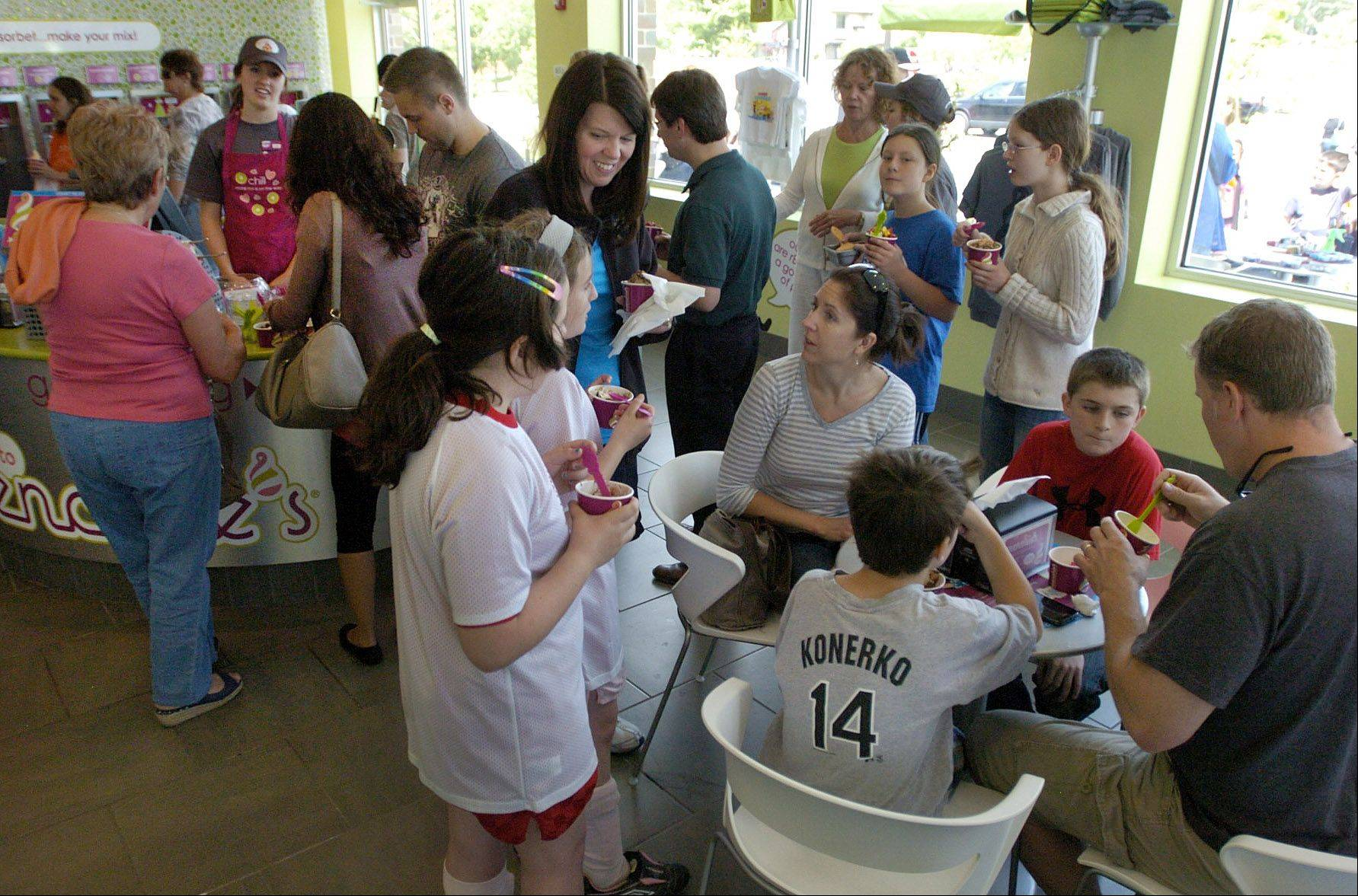 Free frozen yogurt is given to customers at the grand opening of the new Menchie's frozen yogurt in Mount Prospect earlier this month.