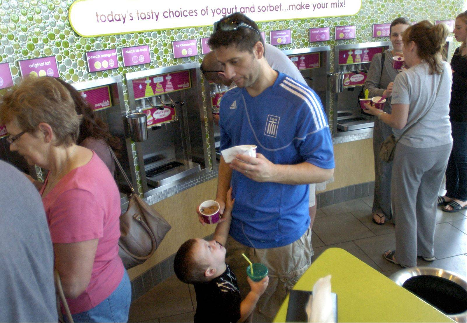Alex Michalakos and his son, Elias, sample some of the free frozen yogurt given out during the grand opening of the new Menchie's frozen yogurt in Mount Prospect June 2.