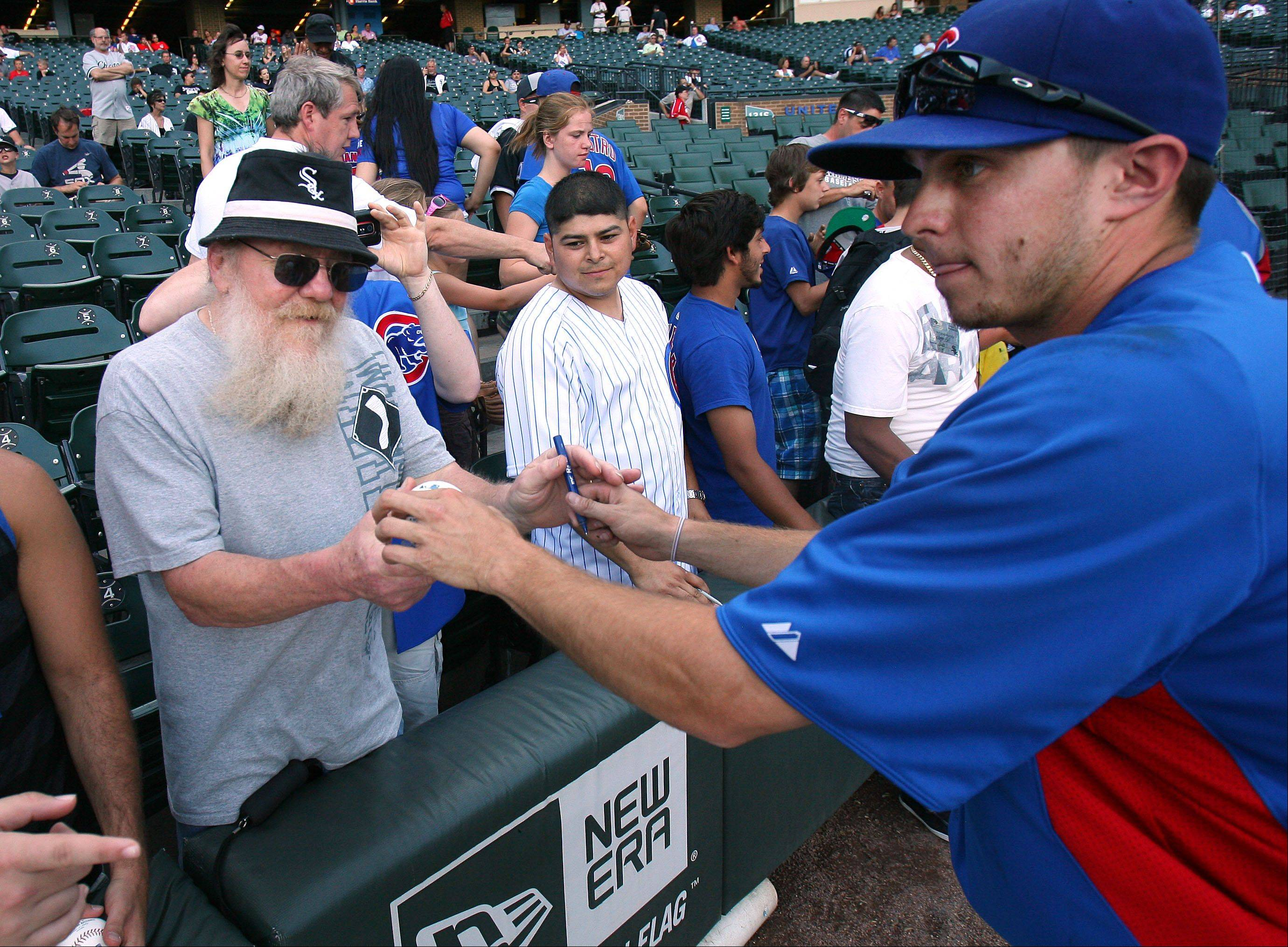 Sox fan Mike Fobes of Chicago gets a ball signed by Chicago Cubs' Tony Campana.