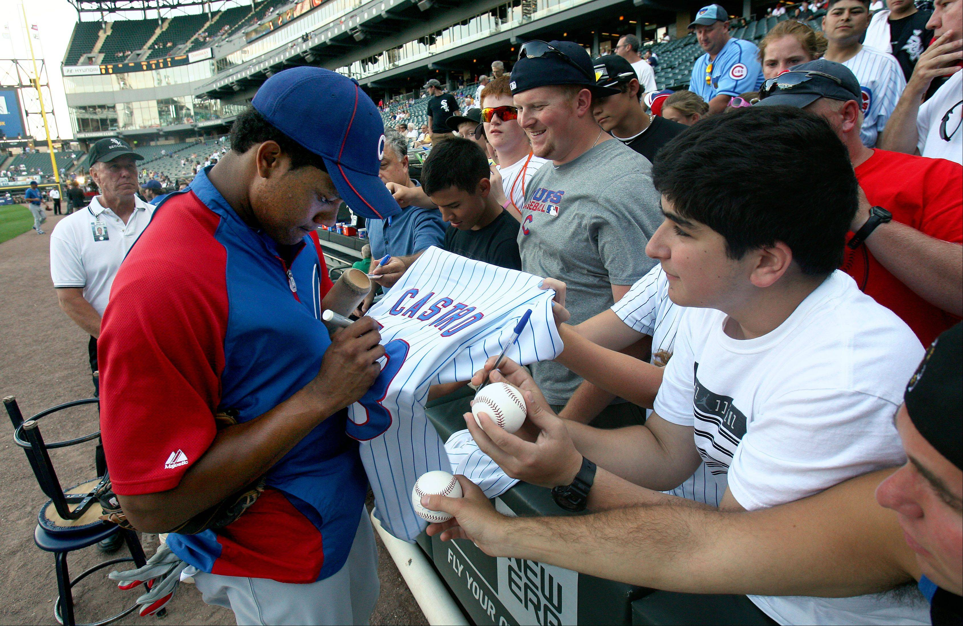 Chicago Cubs' Starlin Castro signs autographs before the game.