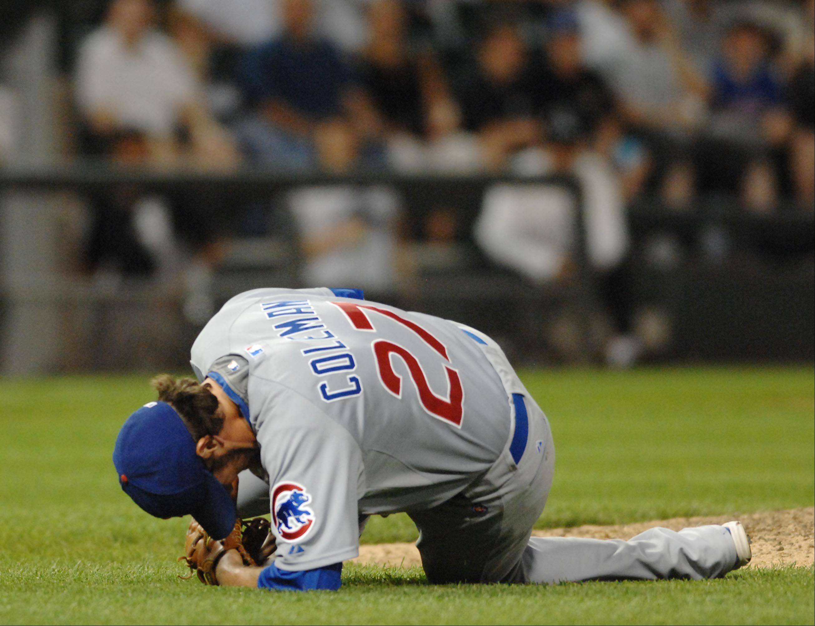 Chicago Cubs relief pitcher Casey Coleman falls to the turf after getting hit with a broken bat in the seventh inning.