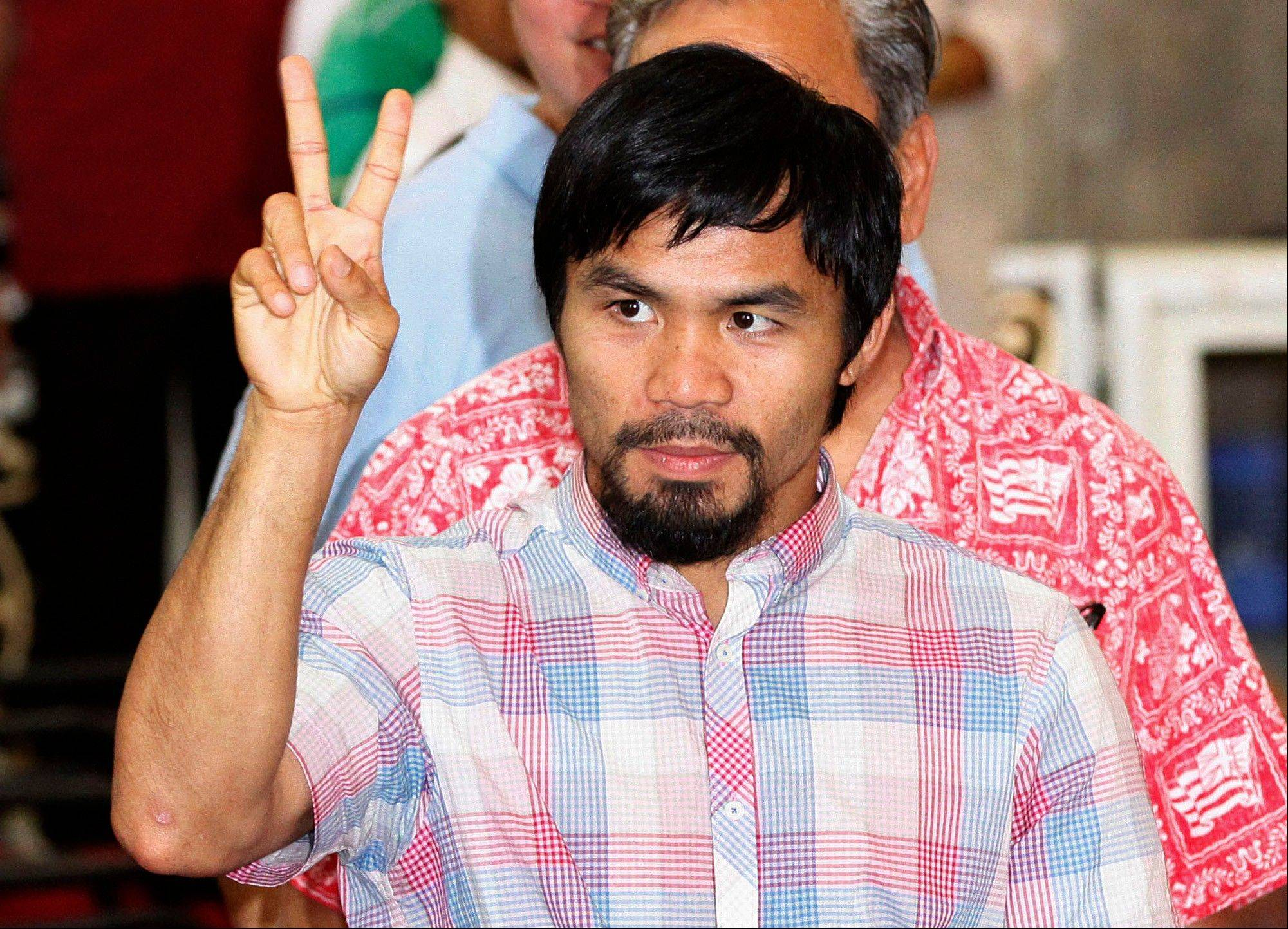 Congressman and former welterweight world champion Manny Pacquiao flashes the sign of peace during a Mass in a Catholic church Saturday in Manila, Philippines. Pacquiao, whose homecoming was much less festive because of his split decision defeat in Las Vegas against American boxer Timothy Bradley, cut short his vacation after the controversial fight to help flood victims in his home province.