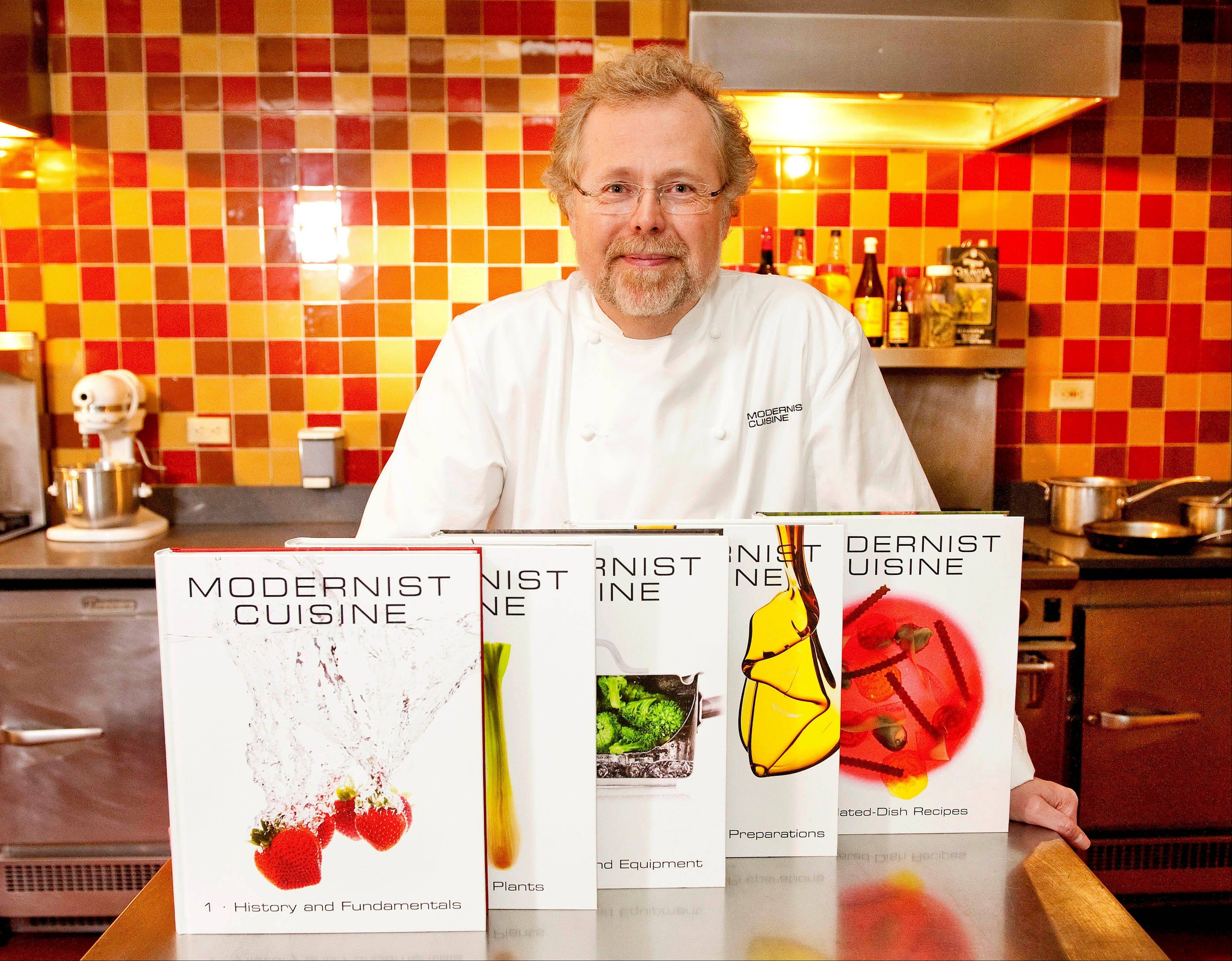 "Nathan Myhrvold, author of ""Modernist Cuisine: The Art and Science of Cooking,"" poses with books from the work at the Institute for Culinary Education in New York on March 23, 2011."