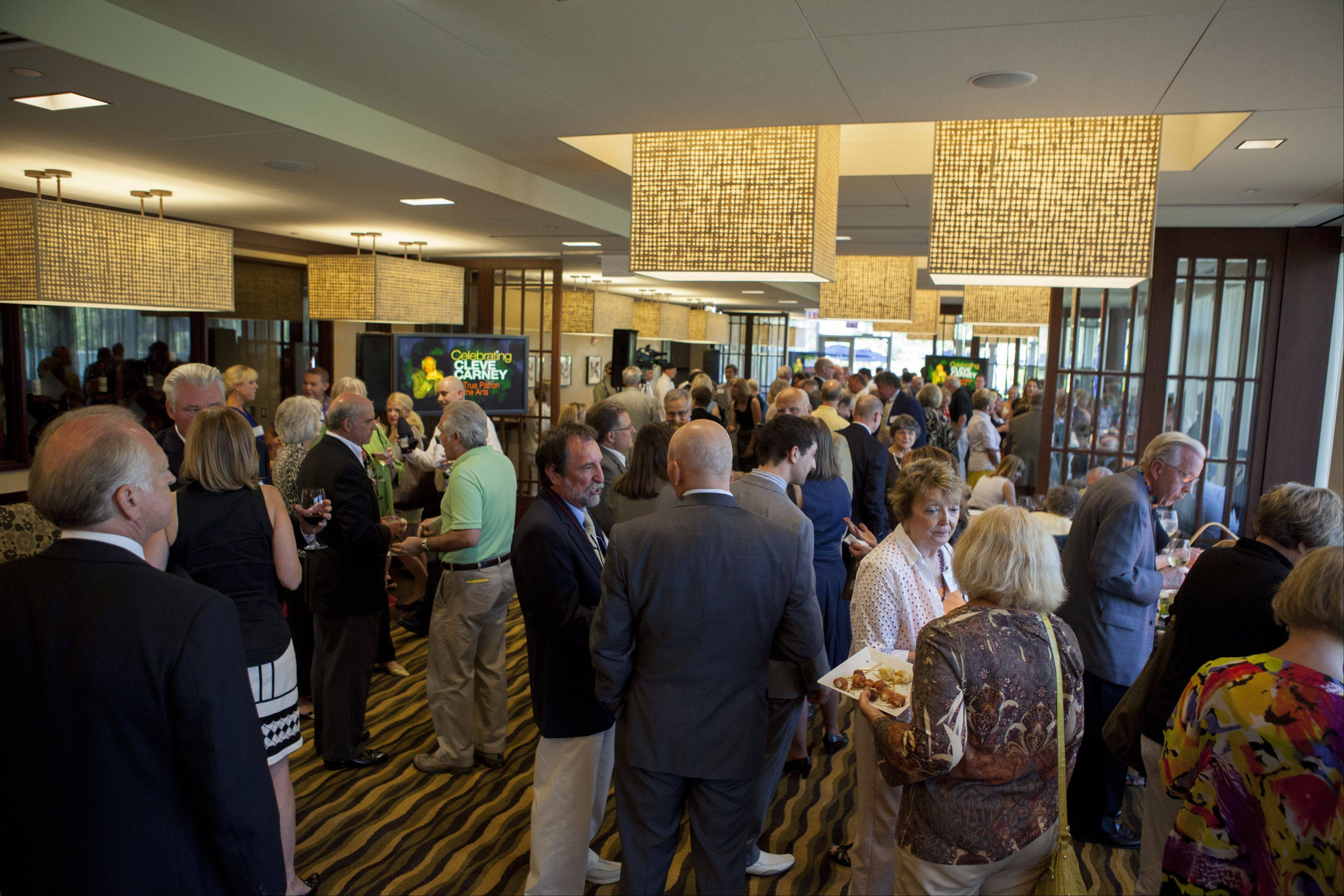 College of DuPage announced the largest gift of $1 million in its 45-year history Thursday night. Friends, family, and patrons of College of Dupage visit with each other during a celebration of Cleve Carney.