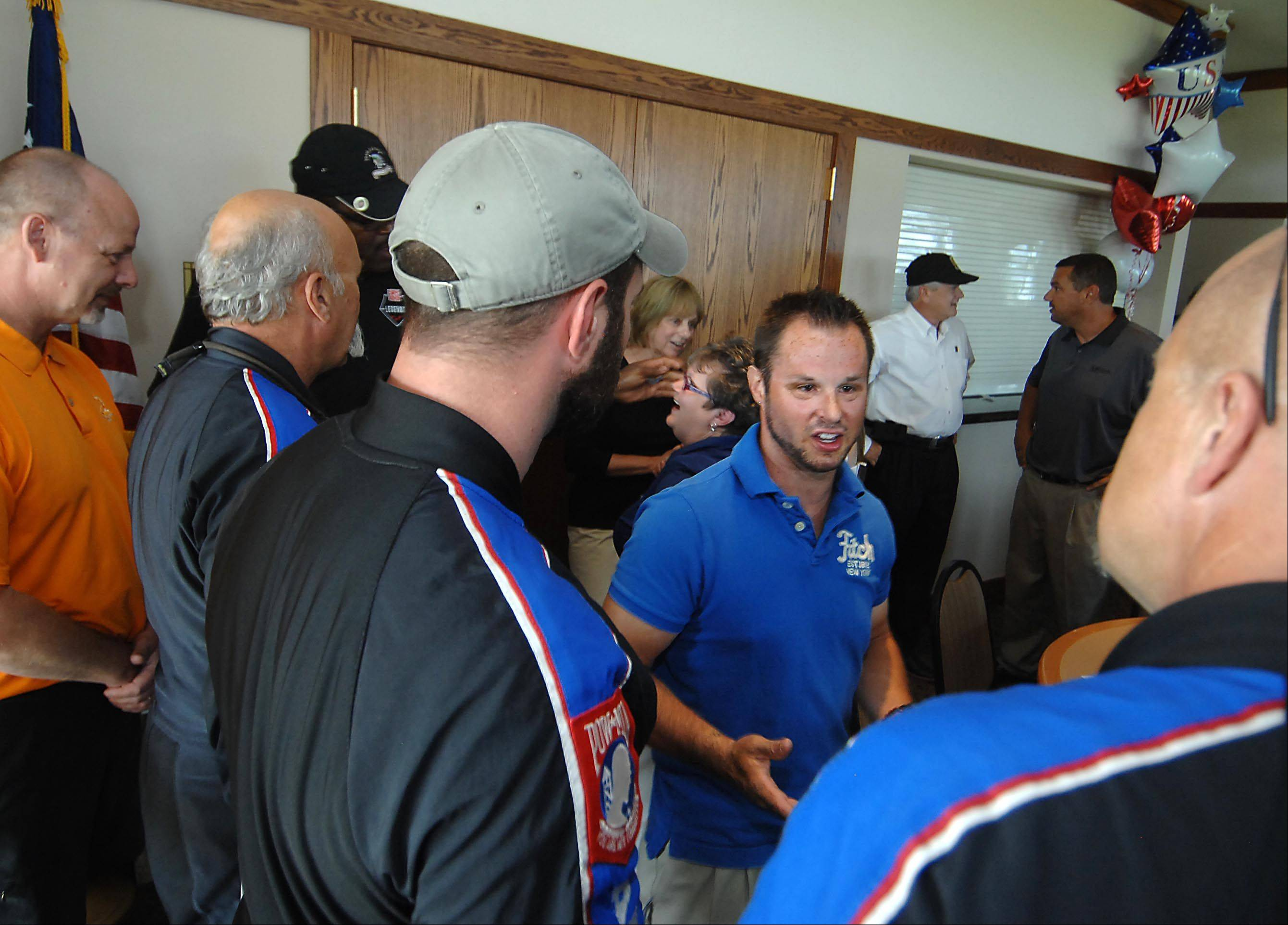 Nick Mapson, 28, talks with skydivers from Team Fastrax Professional Skydiving Thursday after he found out he would be the recipient of a home from the Home Builders Association of Greater Chicago and New American Homes Inc., among a long list of groups that helped with the project.