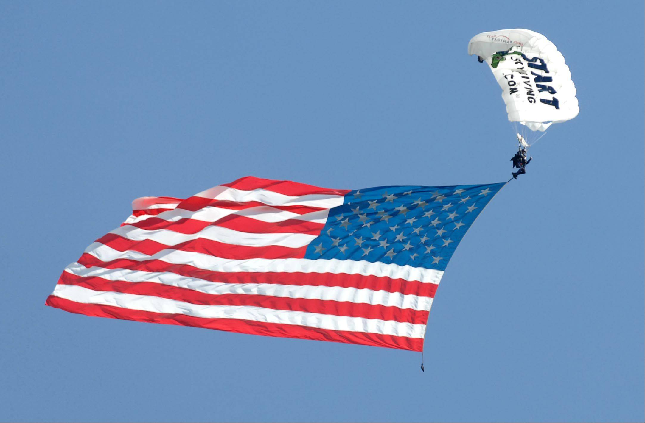 A member of Team Fastrax Professional Skydiving Team brings a large flag down to The Highlands Golf Club Thursday as part of a home giveaway to Nick Mapson, 28, of Sugar Grove and his wife Jackie and son Jaden. Nick is a wounded veteran and was awarded the house by The Home Builders Association of Greater Chicago and New American Homes Inc., among the many groups that helped with the project.