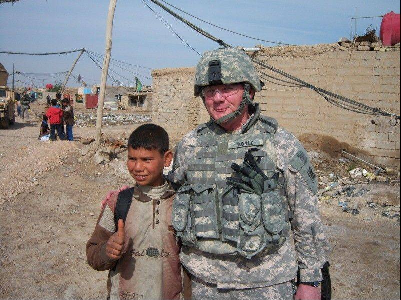 Tom Boyle poses for a photograph with a local boy while serving as a law enforcement professional in Iraq. Boyle, 62, of Barrington Hills, was killed Tuesday during a firefight in Afghanistan.