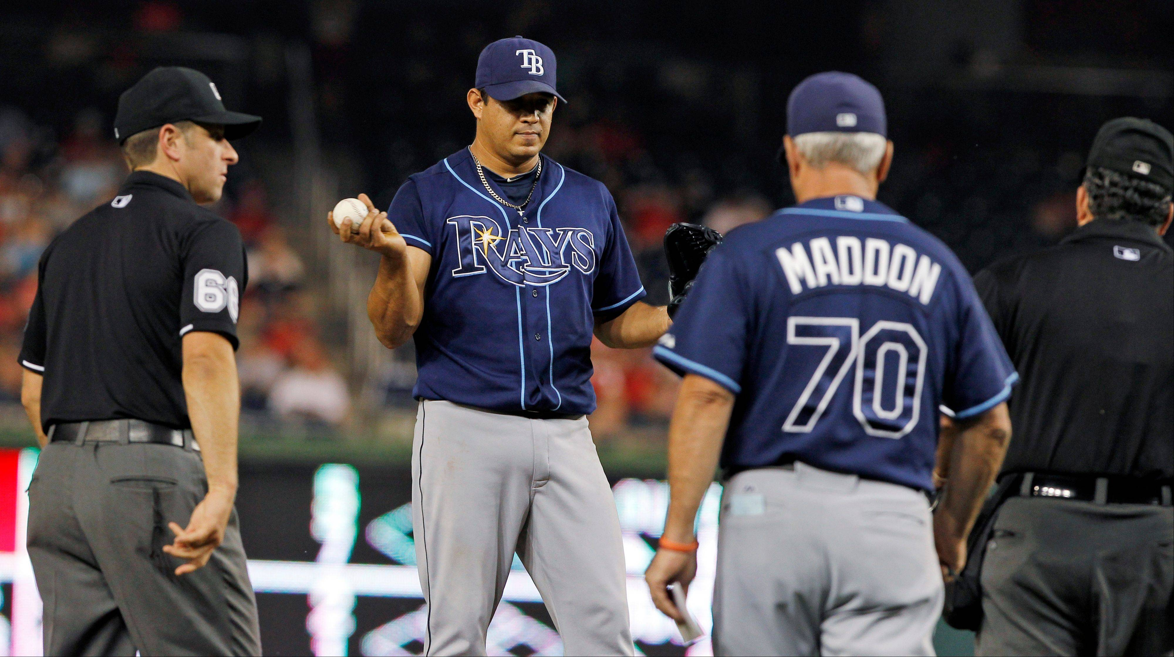 Tampa Bay Rays manager Joe Maddon heads to the mound to talk with relief pitcher Joel Peralta and the umpires Tuesday during the eighth inning against the Washington Nationals at Nationals Park in Washington. Peralta was ejected without throwing a pitch after the umpires found a foreign substance on his glove.