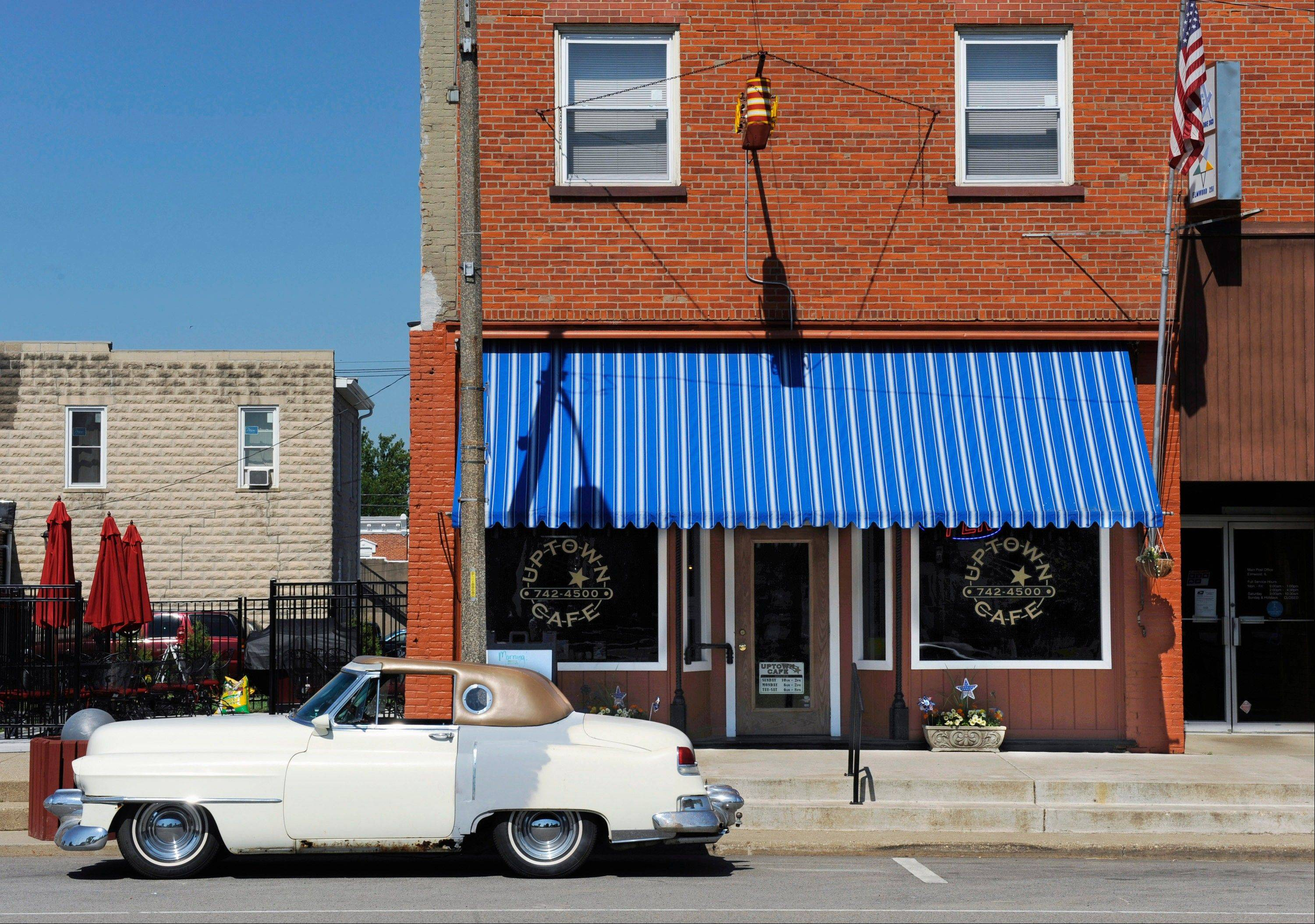 A 1953 Cadillac Fleetwood, modified from a four-door sedan by its owner, Bruce Phelps, stands parked in front of the Uptown Cafe, opened by Shawn and Rita Jones in August, 2011, in downtown Elmwood.