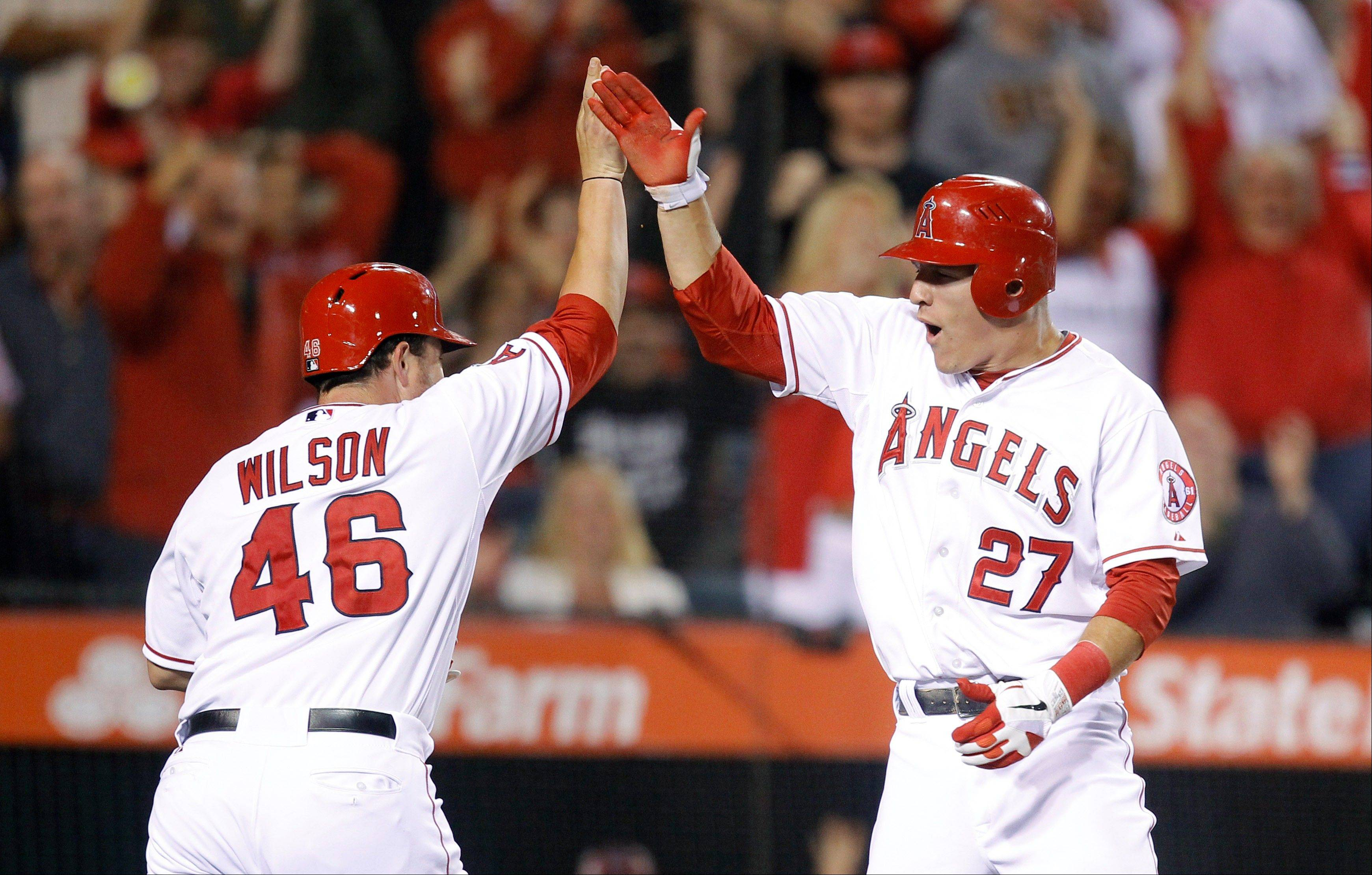 The Angels' Mike Trout, right, and Bobby Wilson high-five after they scored on a single by Torii Hunter in the sixth inning Friday against the Dodgers in Anaheim.