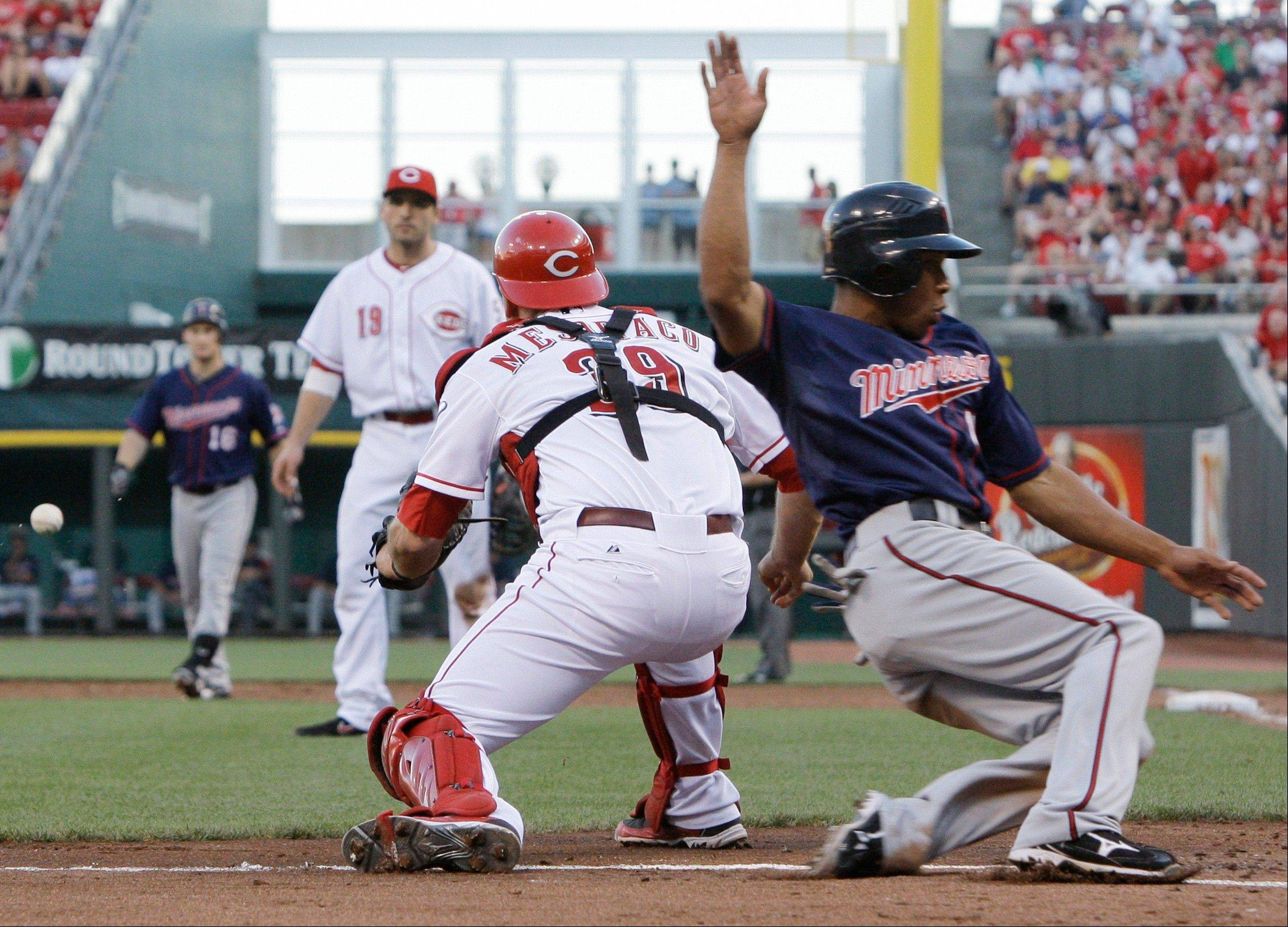 The Minnesota Twins' Ben Revere, right, scores as Cincinnati Reds catcher Devin Mesoraco waits for the throw Friday during the third inning in Cincinnati. Revere scored on a sacrifice fly by Josh Willingham.