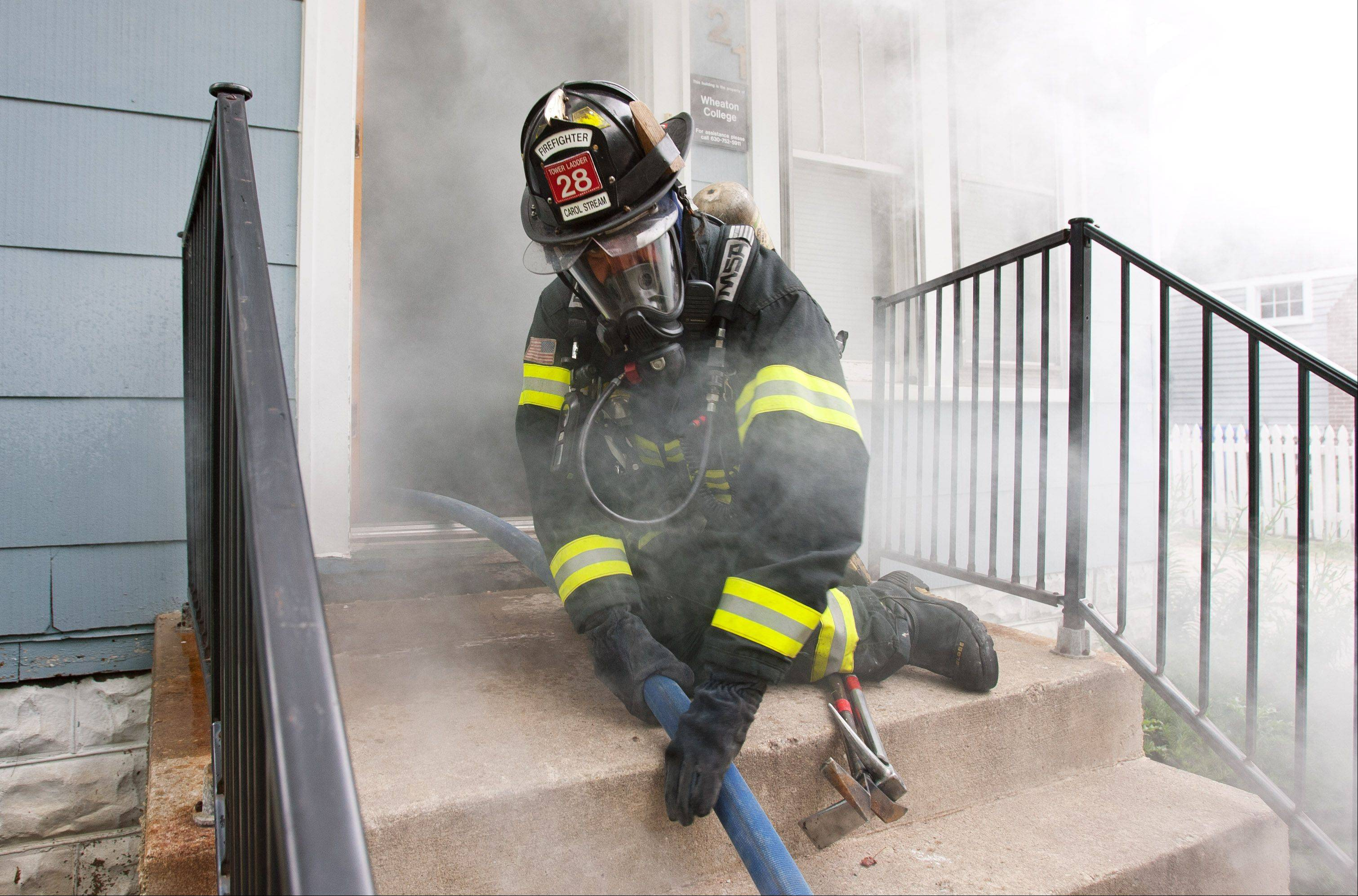 A Carol Stream firefighter pulls in hose, during a cooperative fire training exercise between the Carol Stream, Wheaton, Winfield and West Chicago fire departments.