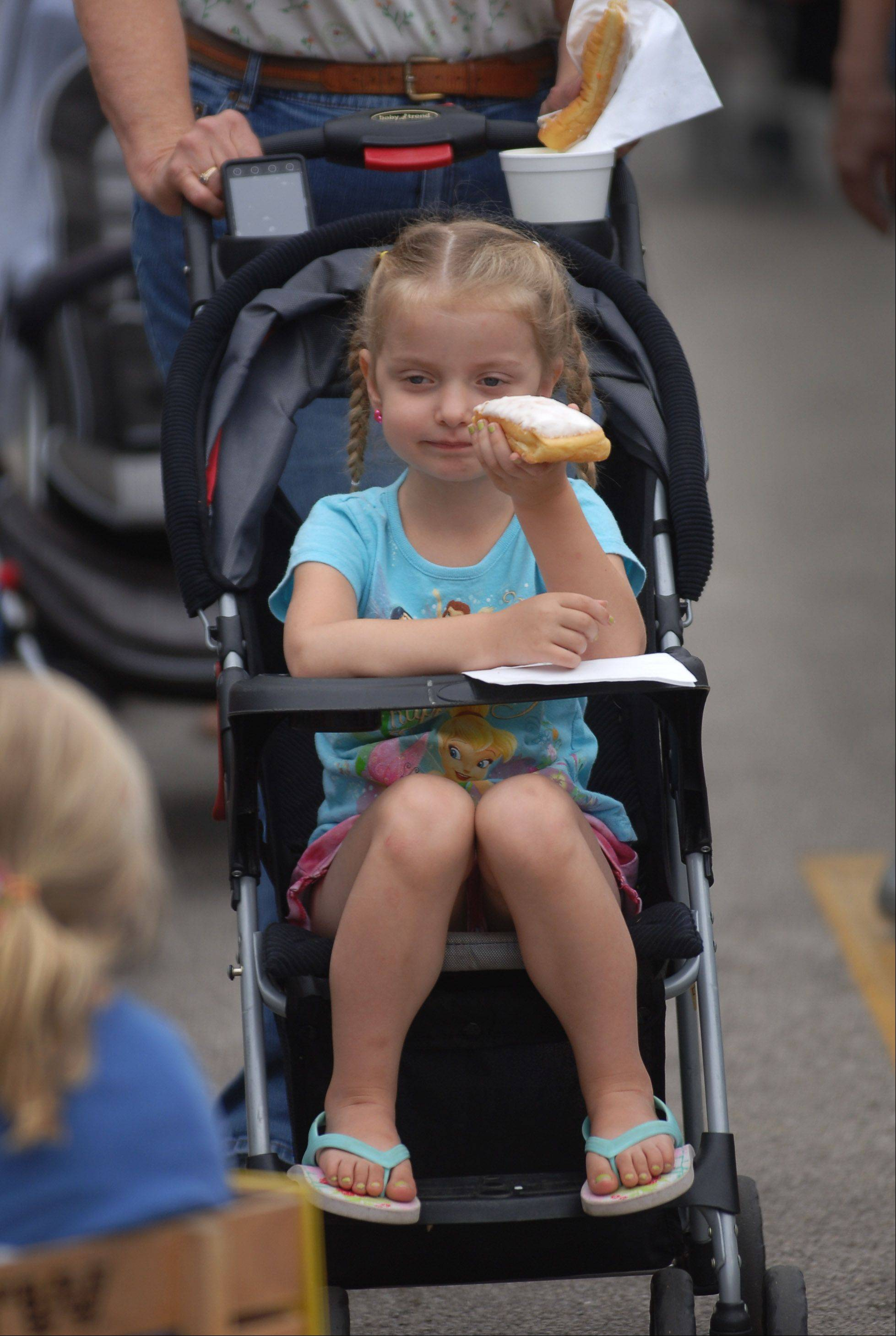 Thursday was the first day of the Libertyville Farmers Market in downtown. Josephine Tilford, 4 of Round Lake Beach, gets ready to dig into a long john doughnut purchased from the St. Lawrence Church booth. The market continues every Thursday morning through October 18.