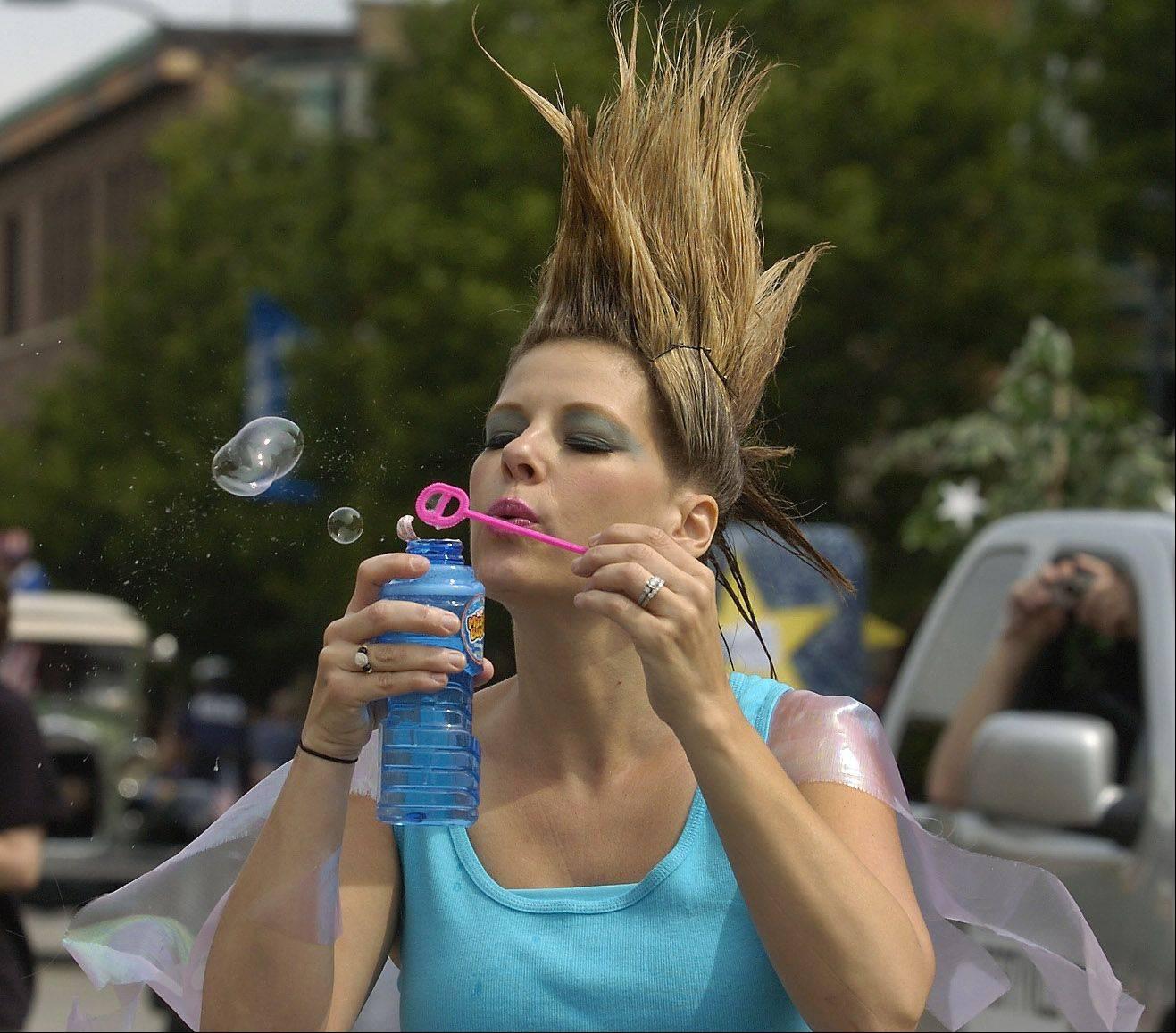 Shelly Malizola of Allure Designs in Beauty, blows bubbles out to parade watchers during the Libertyville Days Parade.