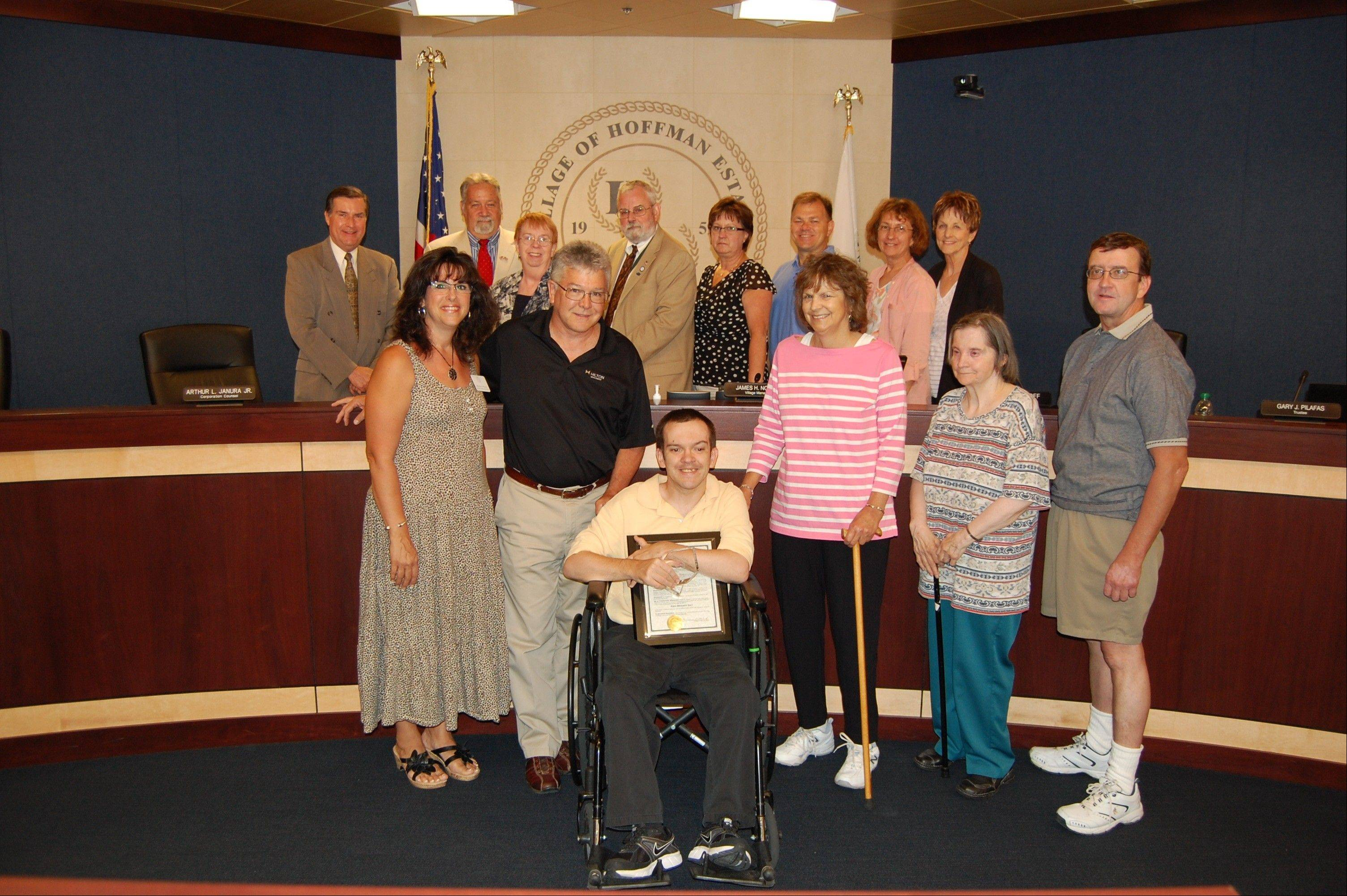 Eric Brandt, this year's recipient of the Barb Basl Award for Disabled Citizens, with the village board, members of the Commission for Disabled Citizens and his parents.