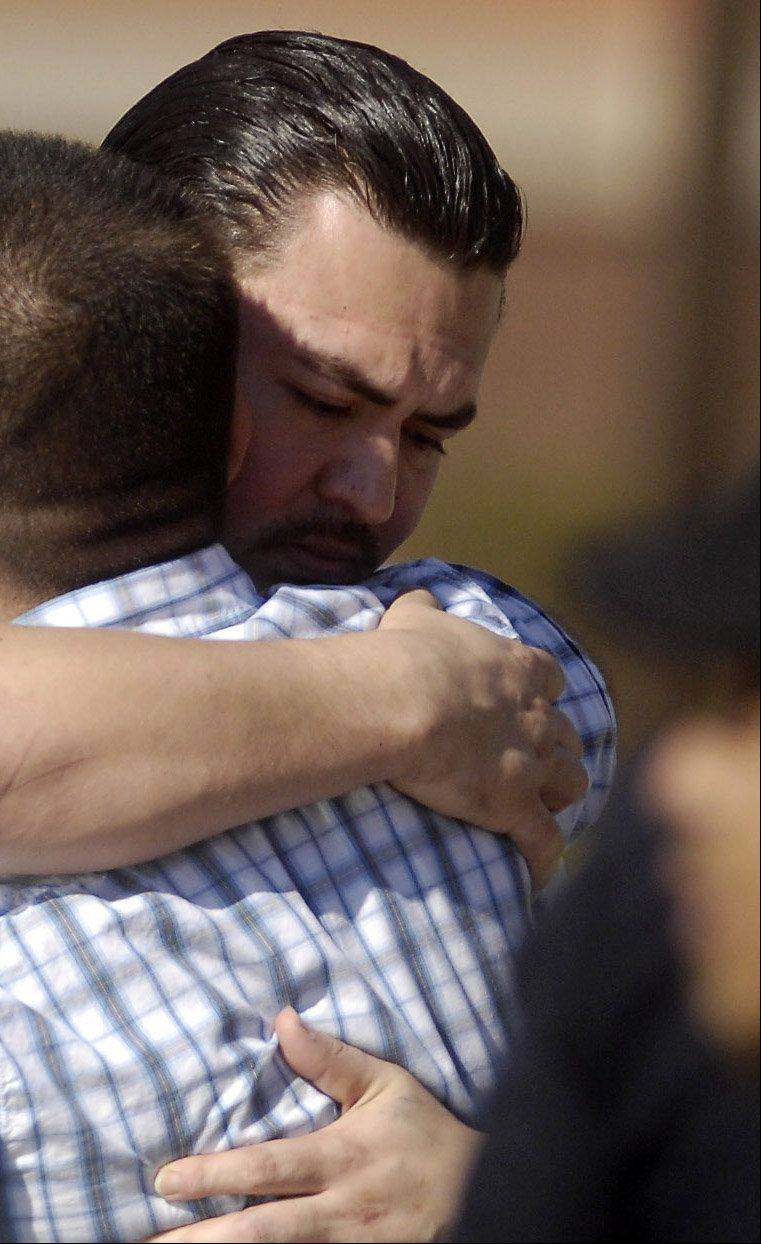 Eric Galarza, right facing, is hugged by a well-wisher following the funeral for his 5-year-old son Eric Jr., who was killed on Oct. 7. Police say he threatened to kill his wife Thursday and managed to escape authorities by fleeing into a state park near Wayne.