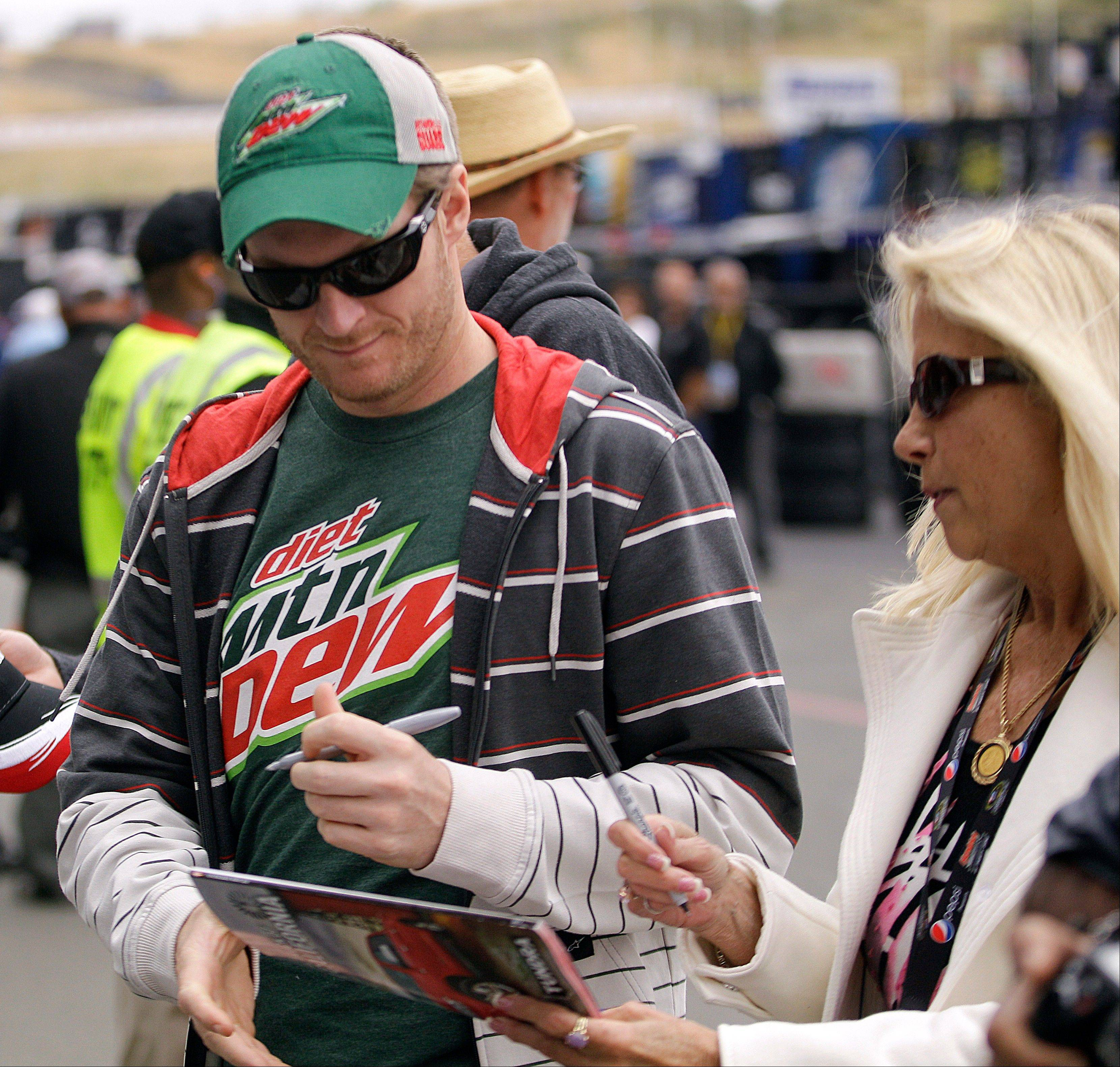 Dale Earnhardt Jr. signs an autograph for a fan prior to taking practice laps for Sunday's NASCAR Sprint Cup Series race in Sonoma, Calif.
