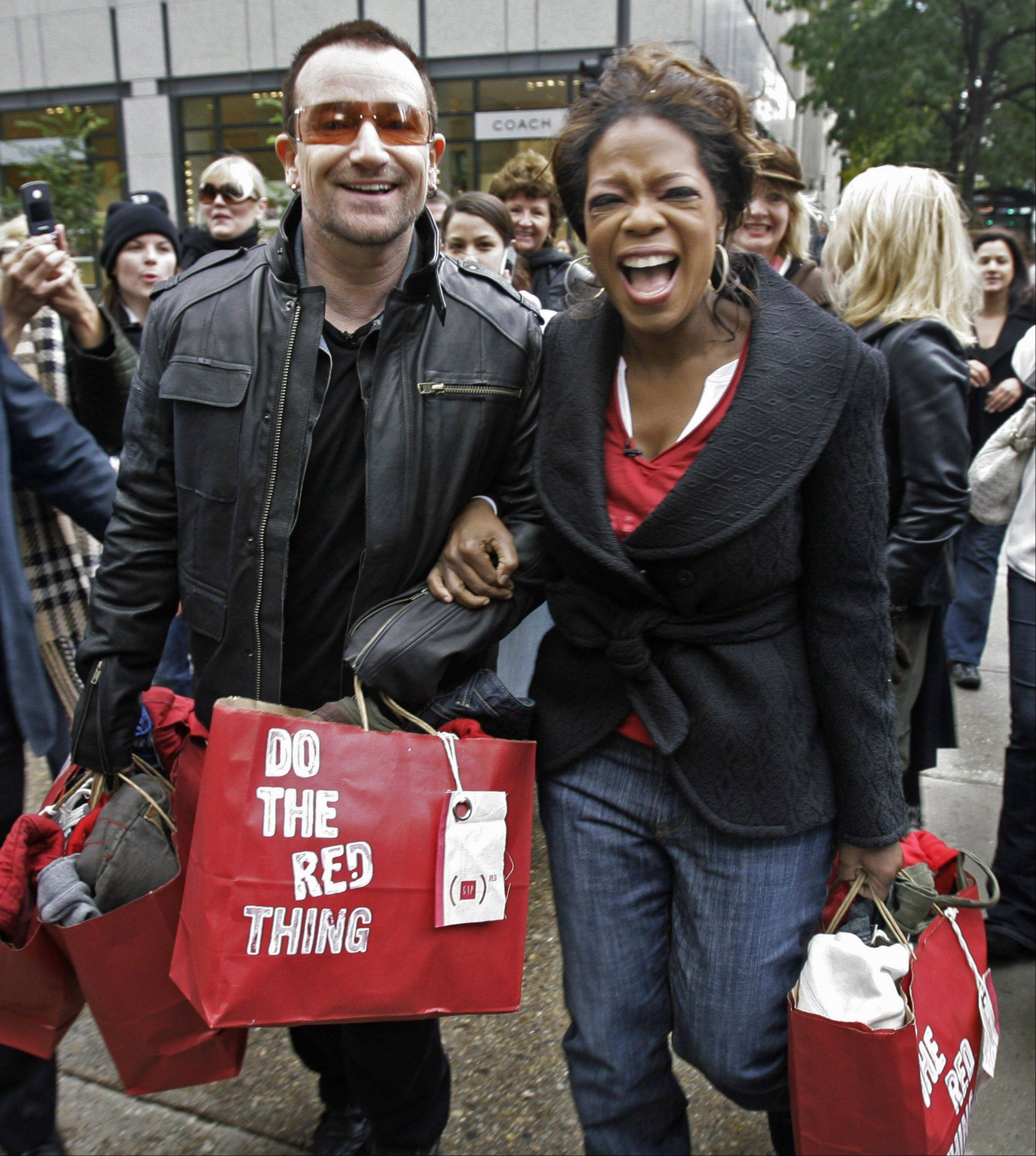 "Irish rocker Bono, frontman for U2, and talk show host Oprah Winfrey walk down Chicago's ""Magnificent Mile"" Thursday, Oct. 12, 2006, for a shopping spree to promote his new Red product line that will be put on sale in the coming weeks by retailers Gap, Apple, Motorola, Converse and Emporio Armani. Gap will donate 50 percent of sales to Bono's Project Red to fight AIDS in Africa."