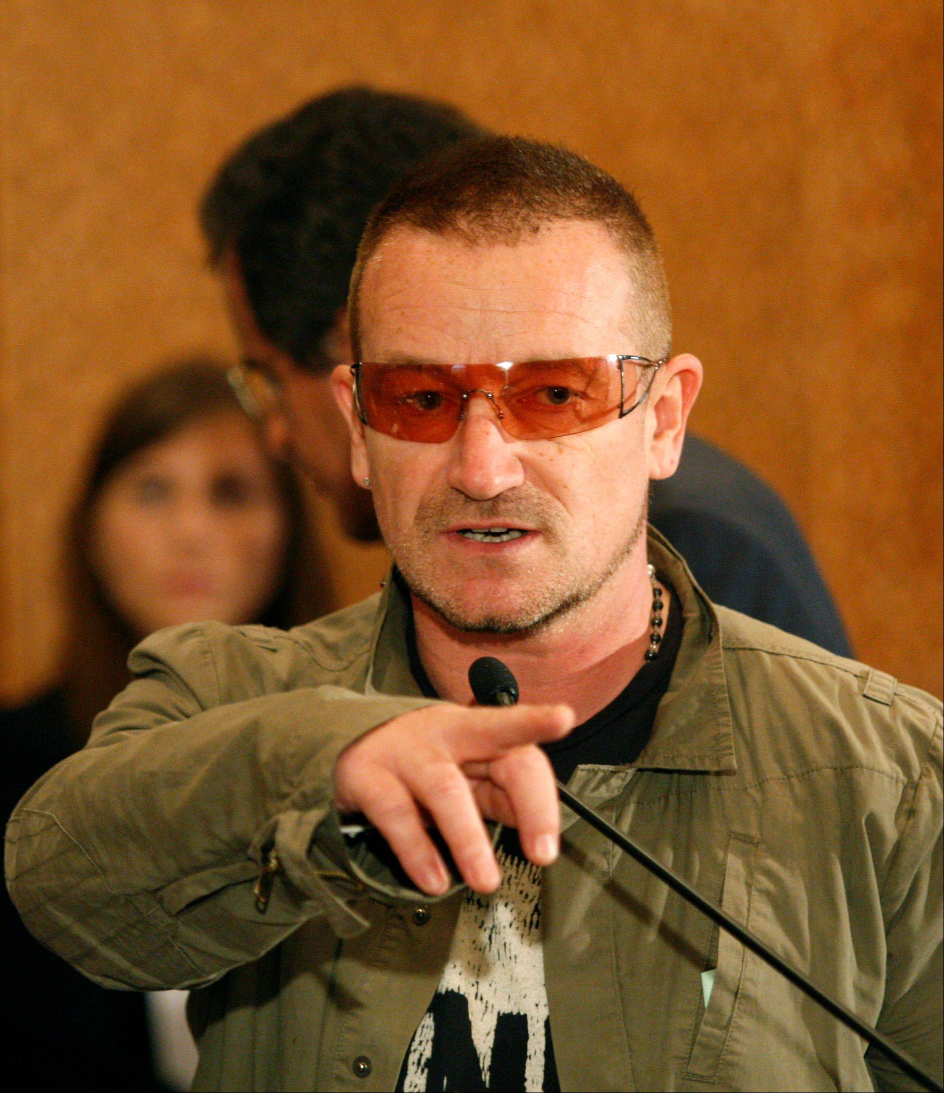 Musician Bono points out other well-known attendees at the United Nations 2008 Millennium Development Goals Malaria Summit in New York, Thursday, Sept. 25, 2008.