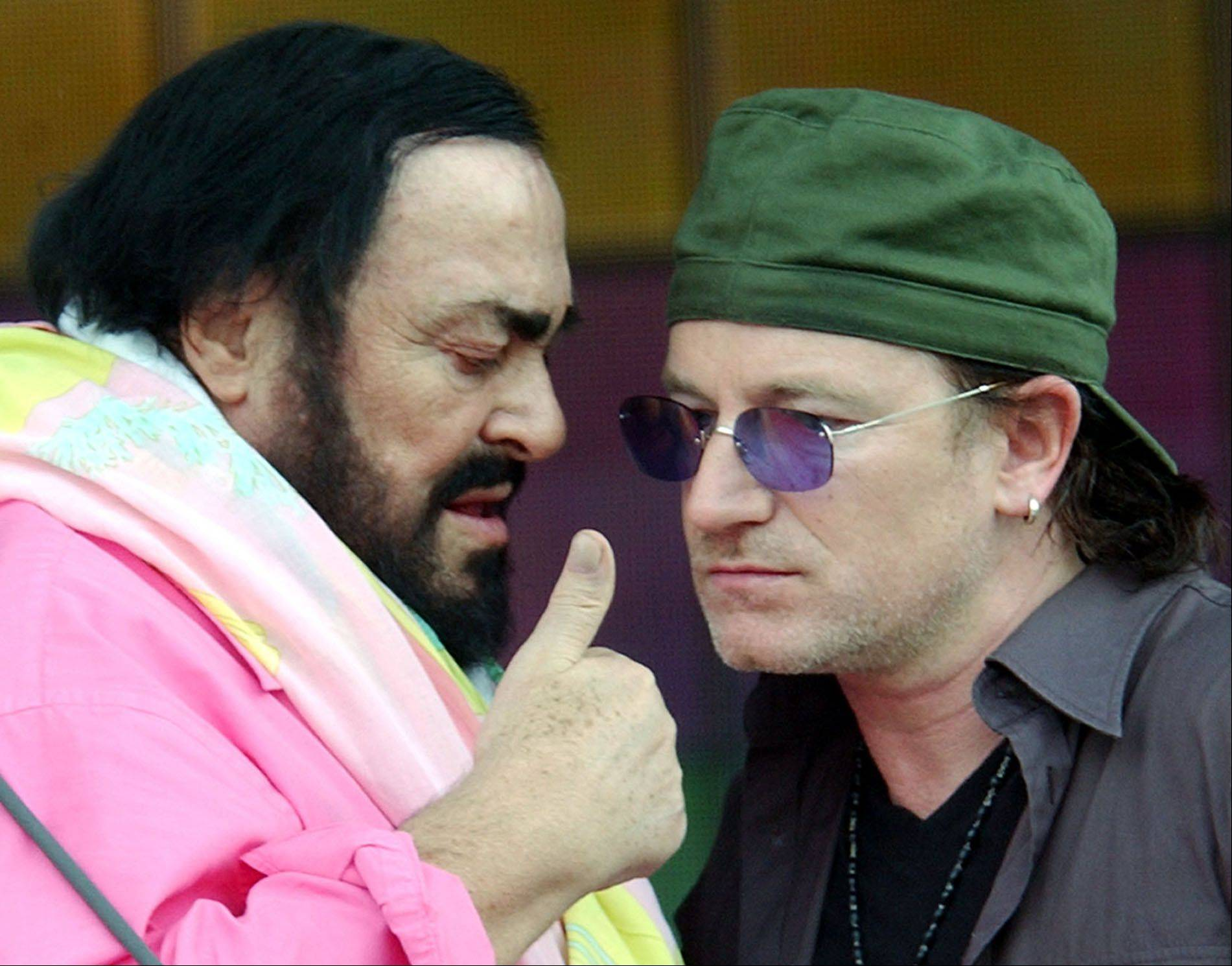 Singer Bono, right, speaks with Italian tenor Luciano Pavarotti during rehearsal for the Pavarotti & Friends 2003 annual charity concert at the Novi Sad Park in Modena, Italy, Monday, May 26, 2003.