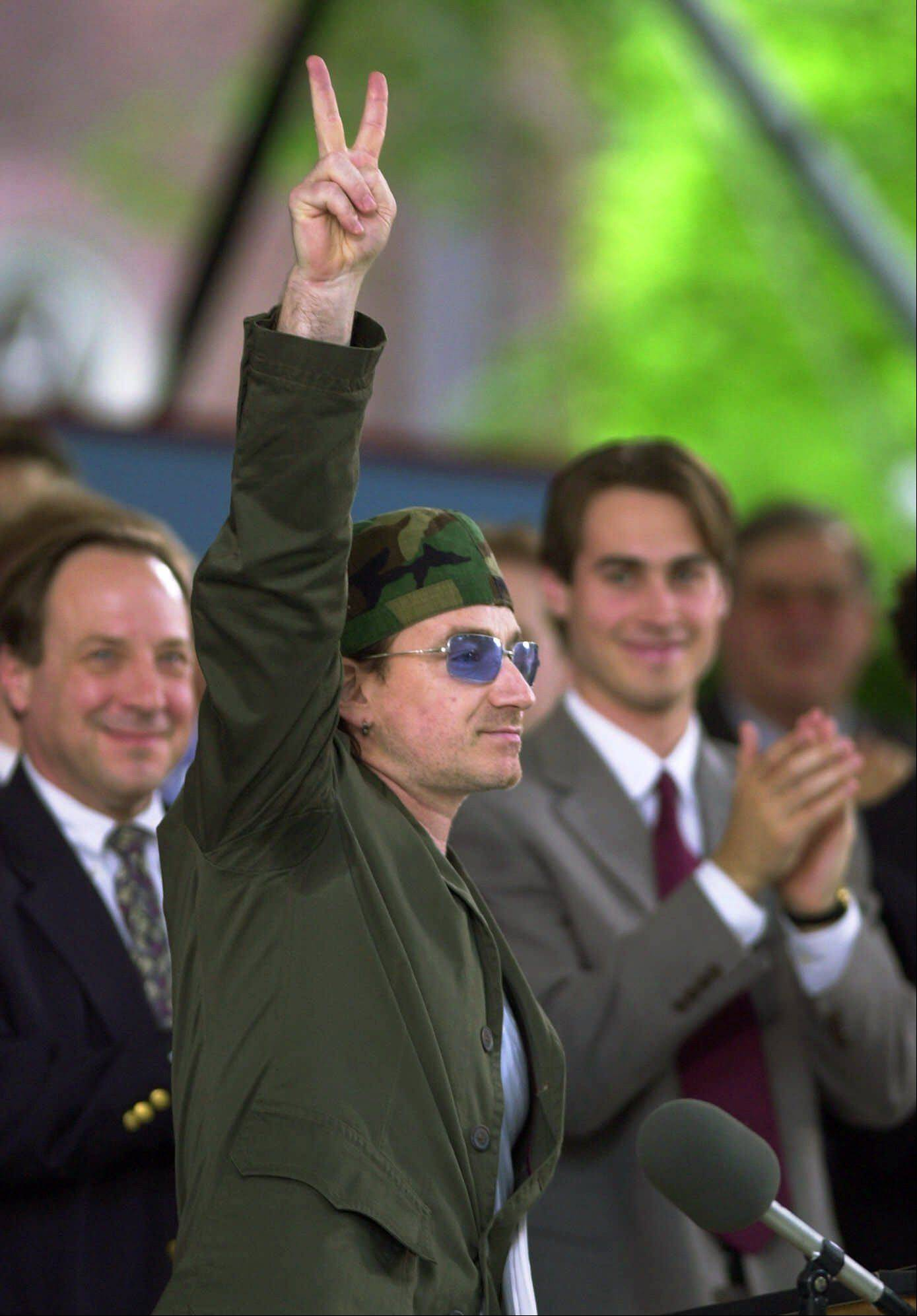 U-2's Bono gestures with the peace sign after delivering the Class Day address at commencement week ceremonies at Harvard University in Cambridge, Mass., Wednesday, June 6, 2001. At far left is Dean of Harvard College, Harry Lewis.