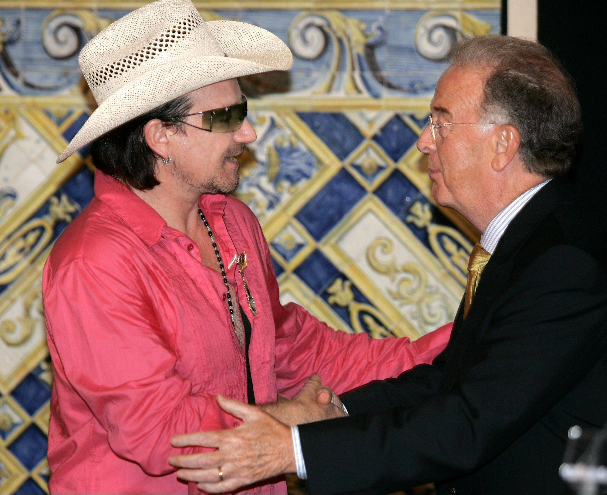 Irish rock band U2 leader Bono, left, shakes hands with Portuguese President Jorge Sampaio, Sunday, Aug. 14, 2005 after being awarded with Portugal's Order of Liberty decoration, one of the country's highest honors, at the Belem presidential palace in Lisbon. The four band members were presented with the medals in recognition of their work for humanitarian causes.