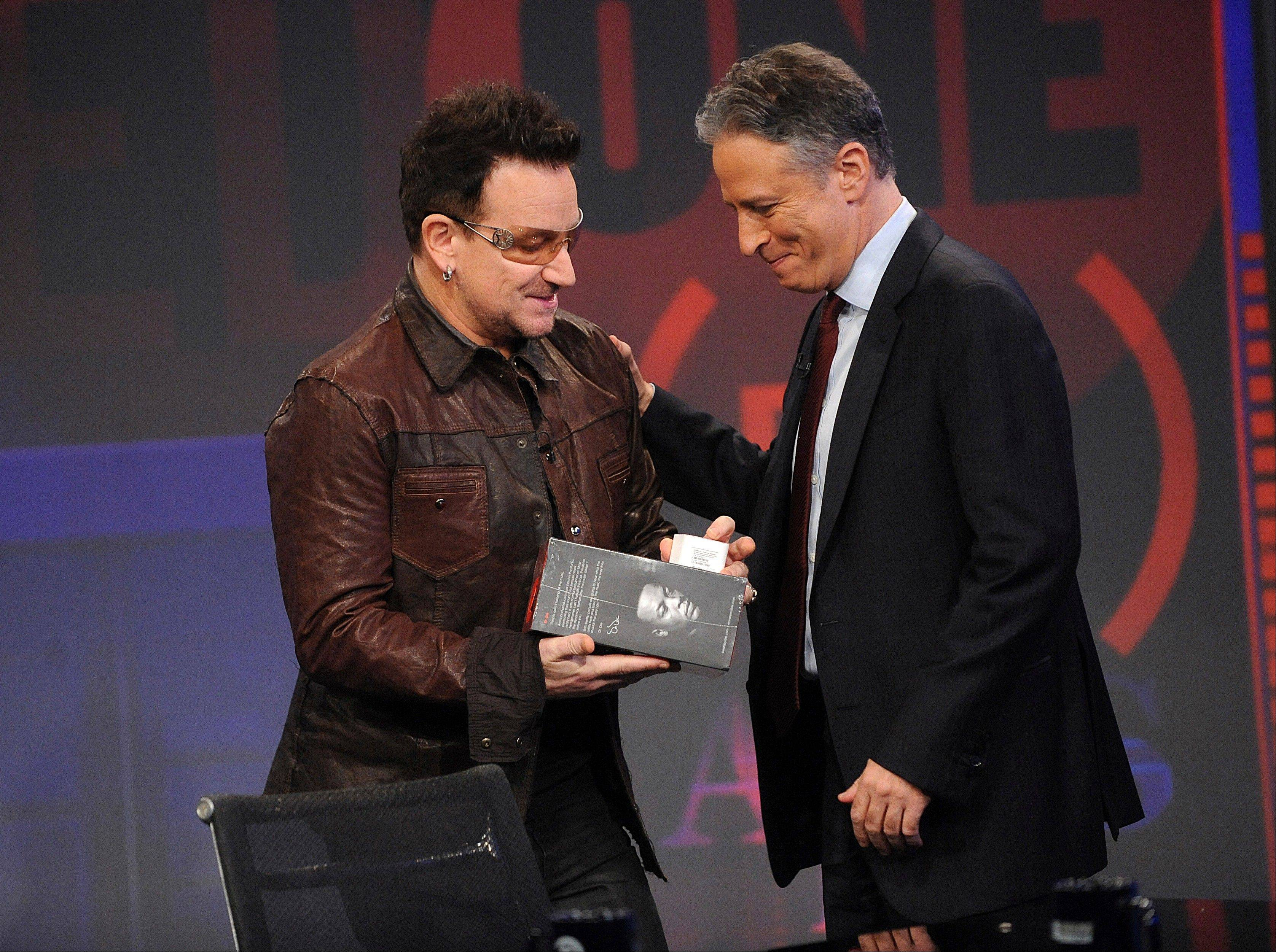 "This Wednesday, Nov. 30, 2011 file photo shows U2 frontman Bono, left, as he presents a pair of headphones to host Jon Stewart during a taping of ""The Daily Show with Jon Stewart"" in New York."
