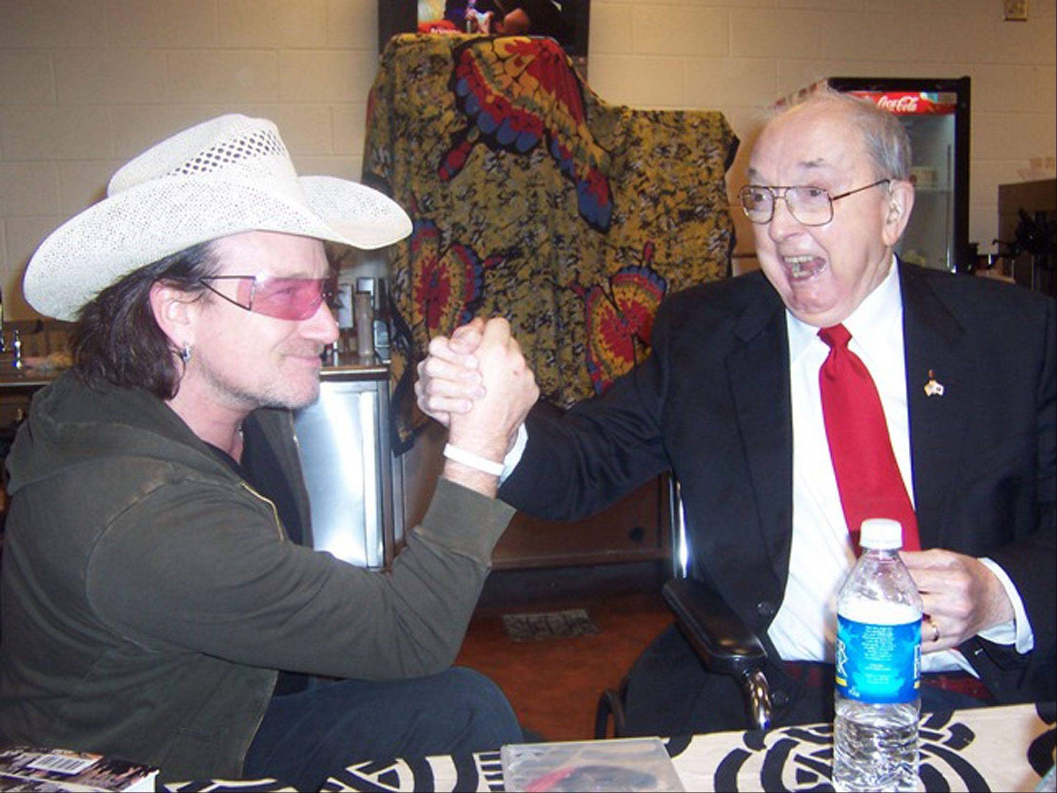 "This photo supplied by the Jesse Helms Center shows Bono, left, of the Irish rock band U2 and former North Carolina Sen. Jesse Helms share a greeting at a preconcert meal at the new Charlotte Bobcats Arena in Charlotte, N.C., before U2 played to a crowd of 17,000 Monday night, Dec. 12, 2005. Since they were introduced several years ago, the archconservative Republican known as ""Senator No"" and Bono have become close allies in the fight against the AIDS epidemic in Africa."