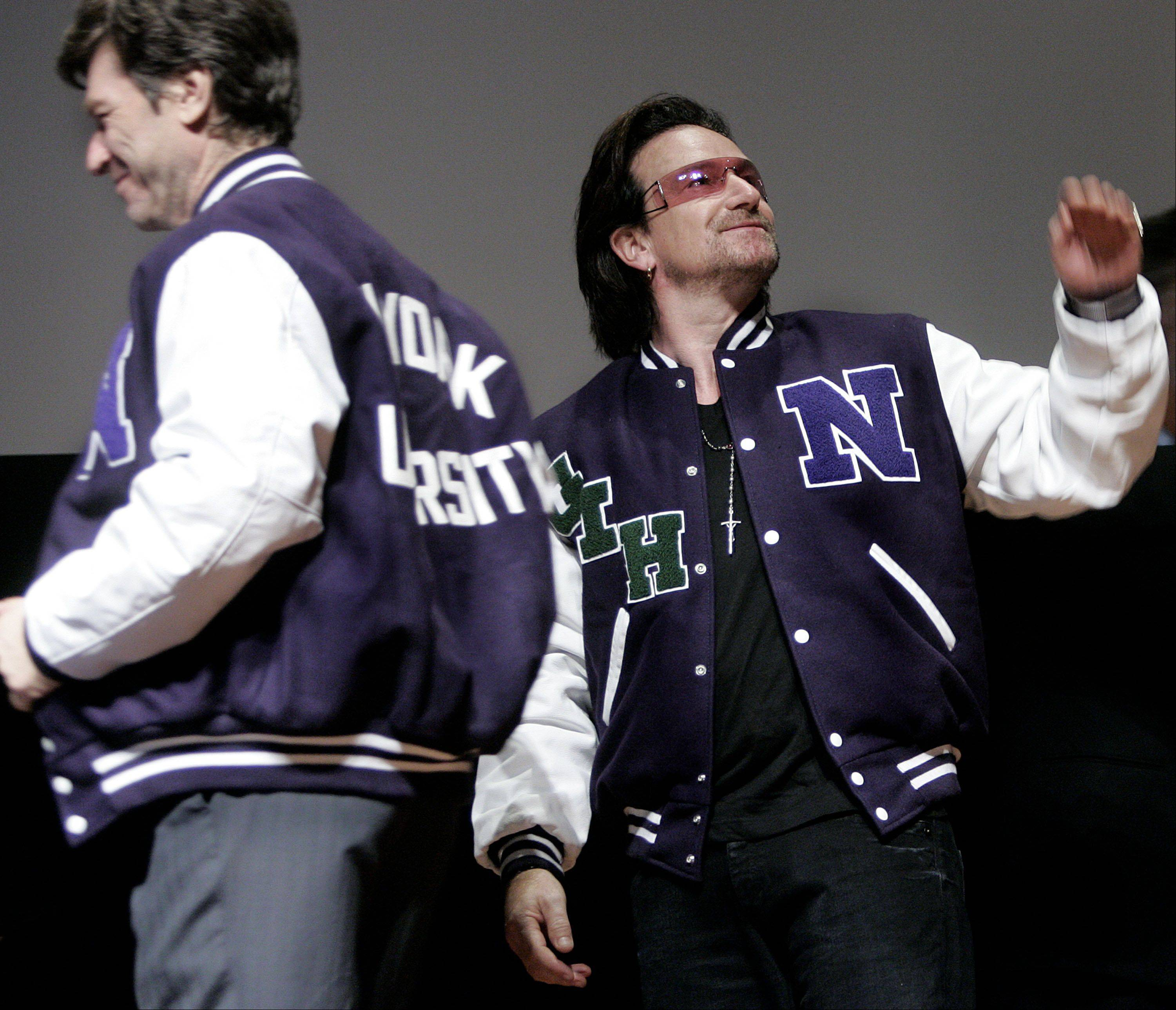 U2's Bono, right, turns to wave as he and Dr. Jeffrey Sachs, left, sport their new NYU jackets after the inaugural Daniel Patrick Moynihan lecture series, Wednesday, Oct. 5, 2005 at New York University in New York. Introduced by Bono fellow activist Dr. Jeffrey Sachs spoke about the eradication of poverty and Third World debt relief.