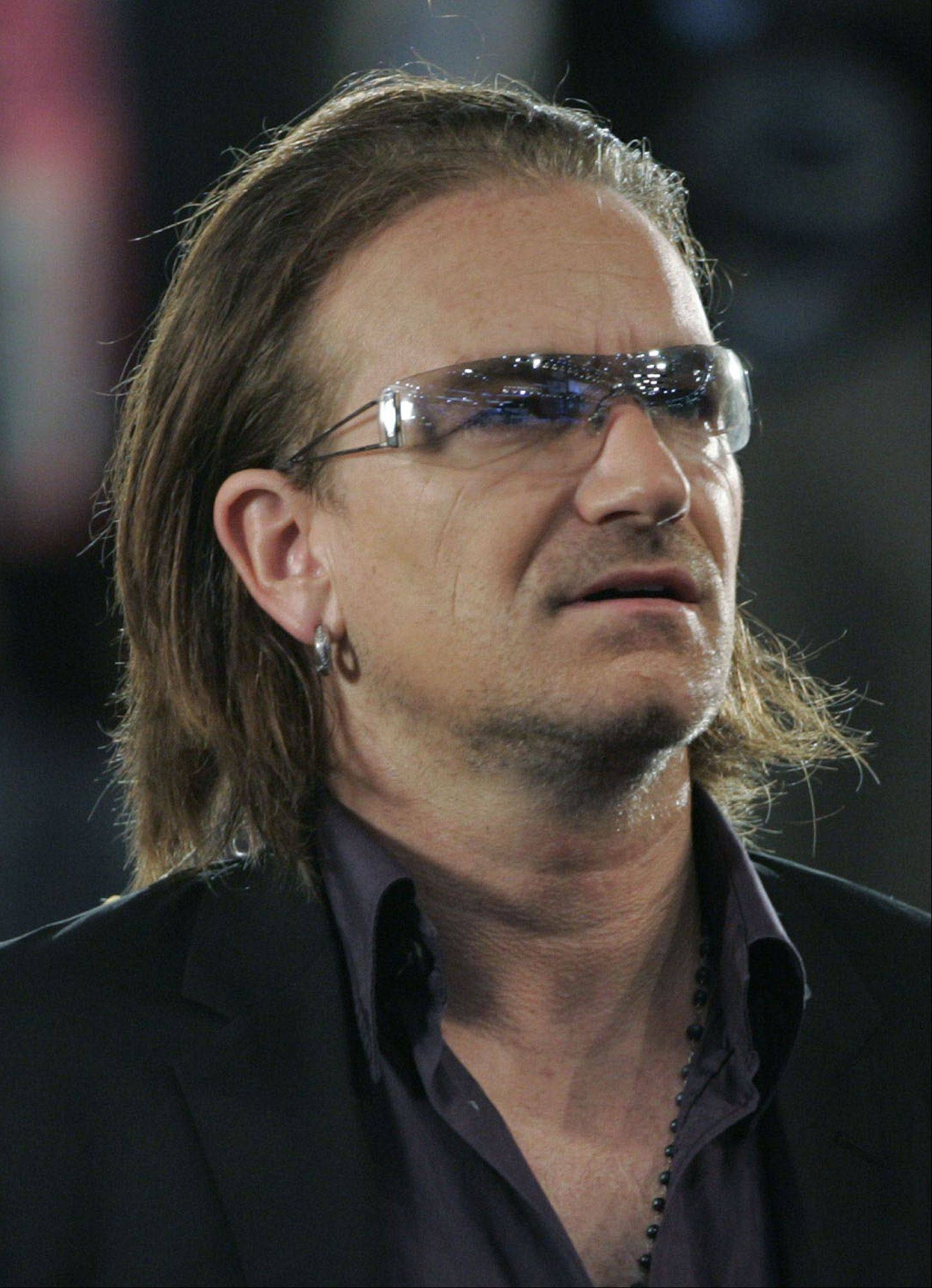 U2's lead singer and activist Bono listens to poet Maya Angelou speak Tuesday, July 27, 2004, at the FleetCenter in Boston during the Democratic National Convention. Bono sang at a private funeral for Susan Buffett, wife of billionaire investor Warren Buffett on Monday, Aug. 2, 2004.