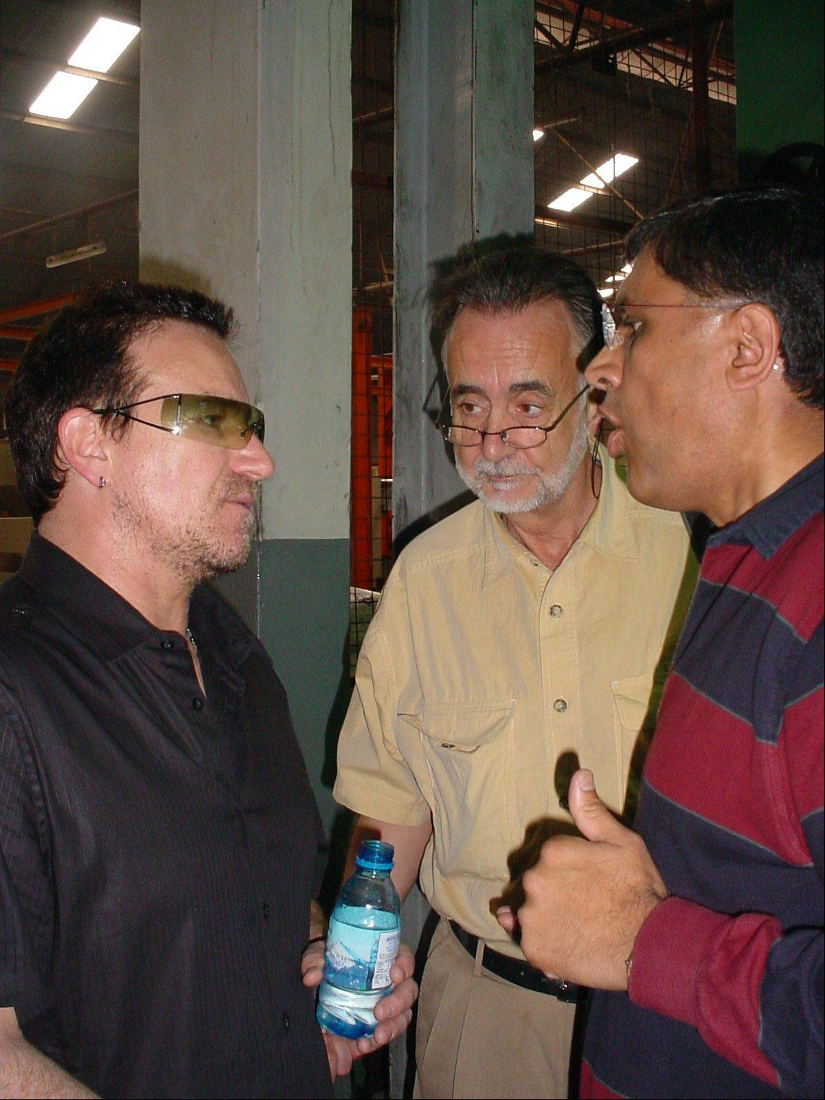U2's lead singer, Bono, left, talks with CEO of A to Z textiles Mills, Anuj Shah, right and Richard Faechemin, Executive Director of The Global Fund, in Arusha, Tanzania on Saturday May, 20, 2006. Bono visited the factory which is the only manufacturer in Africa to make insectile treated nets to fight malaria. The 46-year-old Irish rocker, who has long complained that Africa's problems get little attention in the news, is on a 10-day tour of Africa that's already taken him to South Africa, Rwanda and Lesotho. He also planned stops in Nigeria, Mali and Ghana.