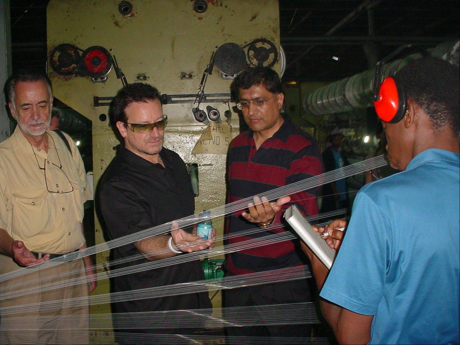 U2's lead singer Bono, second left, observes the weaving process of an insecticide treated net that fights malaria at the A to Z Textile Mills factory in Arusha, Tanzania on Saturday May 20, 2006 in the only factory in Africa, manufacturing such nets. The 46-year-old Irish rocker, who has long complained that Africa's problems get little attention in the news, is on a 10-day tour of Africa that's already taken him to South Africa, Rwanda and Lesotho. He also planned stops in Nigeria, Mali and Ghana.
