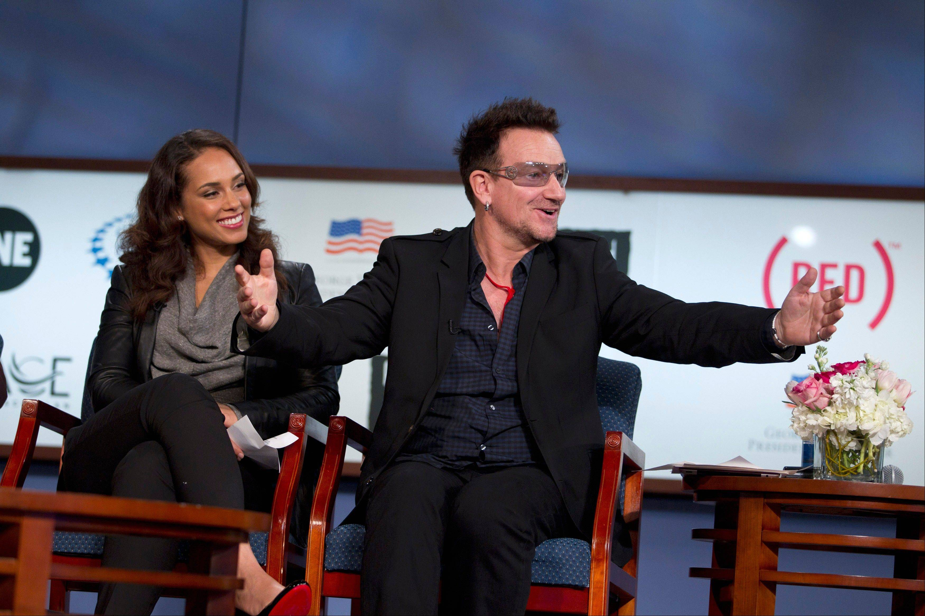 Musicians Bono, right, and Alicia Keys take part in a panel discussion on World AIDS Day, Thursday, Dec. 1, 2011, at George Washington University in Washington.