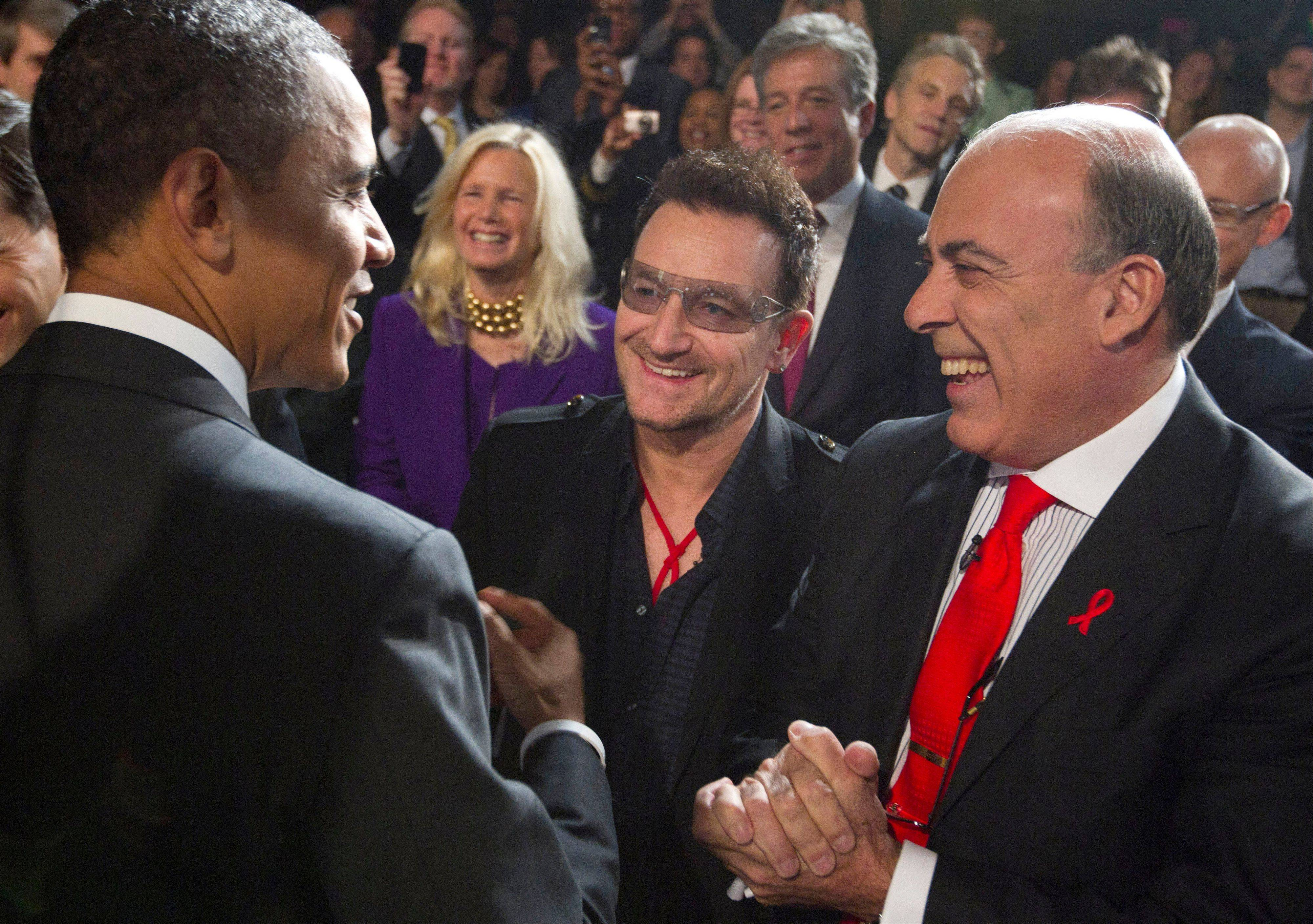 President Barack Obama greets U2 frontman Bono, center, and Muhtar Kent, chairman of the Board and chief executive officer of The Coca-Cola Company, right, after speaking during a World AIDS Day event at George Washington University in Washington, Thursday, Dec. 1, 2011.