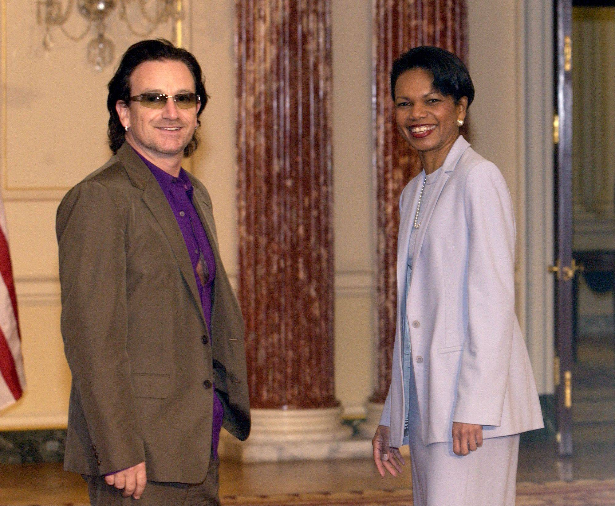Secretary of State Condoleezza Rice, right, poses for photographers with U2 lead singer Bono prior to their lunch at the State Department in Washington, Wednesday, May 25, 2005.