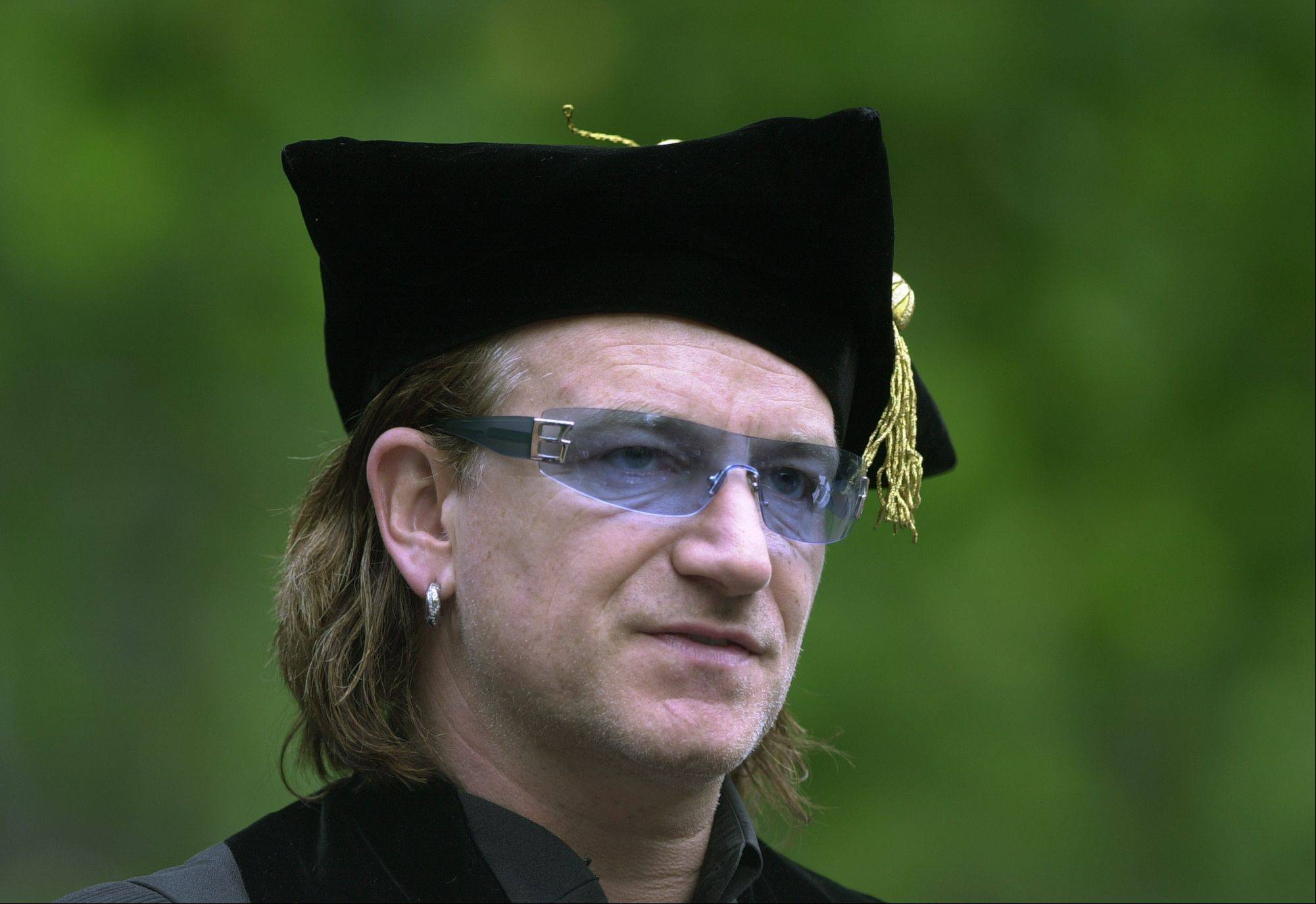 Bono, lead singer of the rock group U2, watches University of Pennsylvania graduate candidates walk toward their commencement ceremony in Philadelphia, Monday, May 17, 2004. Bono delivered the commencement address at the ceremony during which he was also awarded an honorary Doctor of Laws degree.