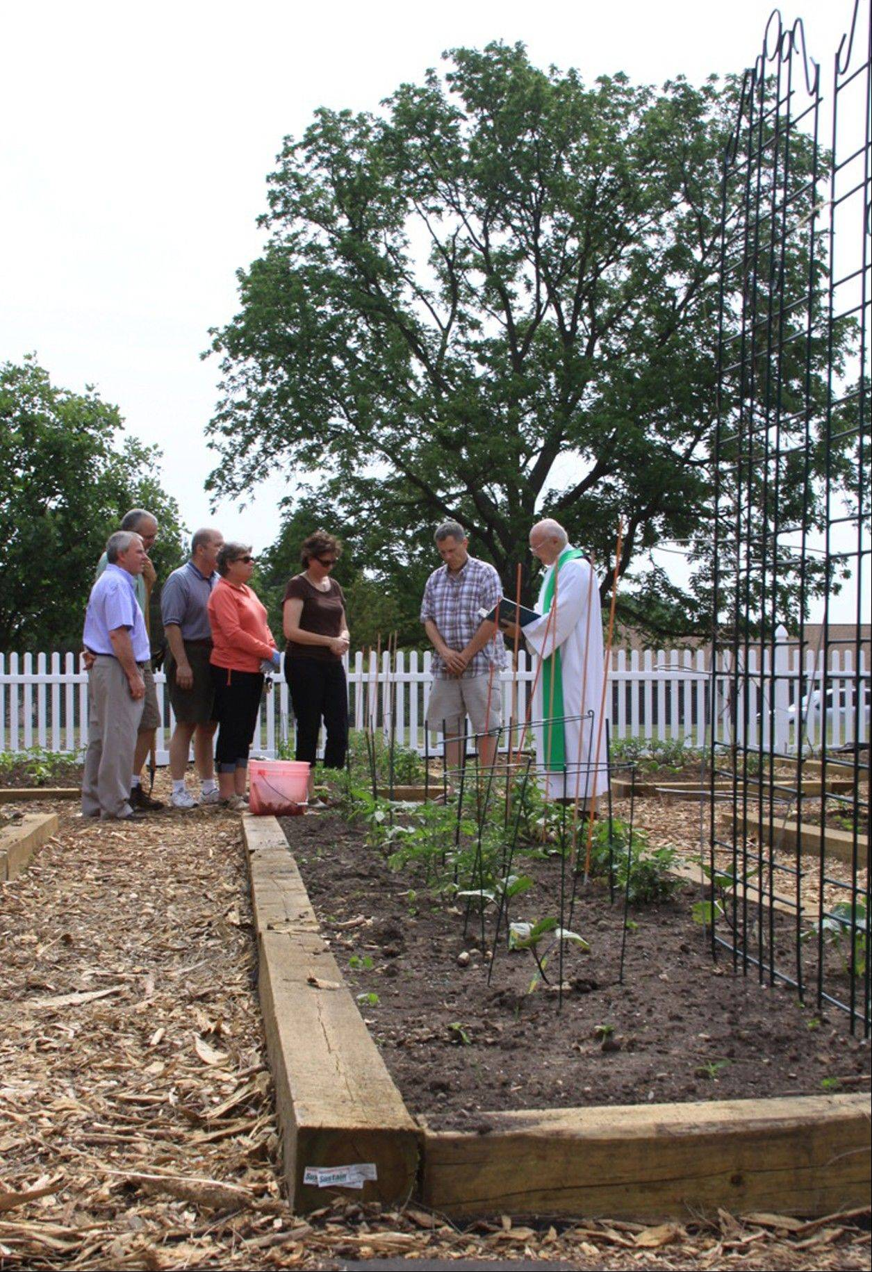 The Rev. Dan Hall of the Clerics of St. Viator, gathers some of the gardeners for a blessing of their garden and their efforts.