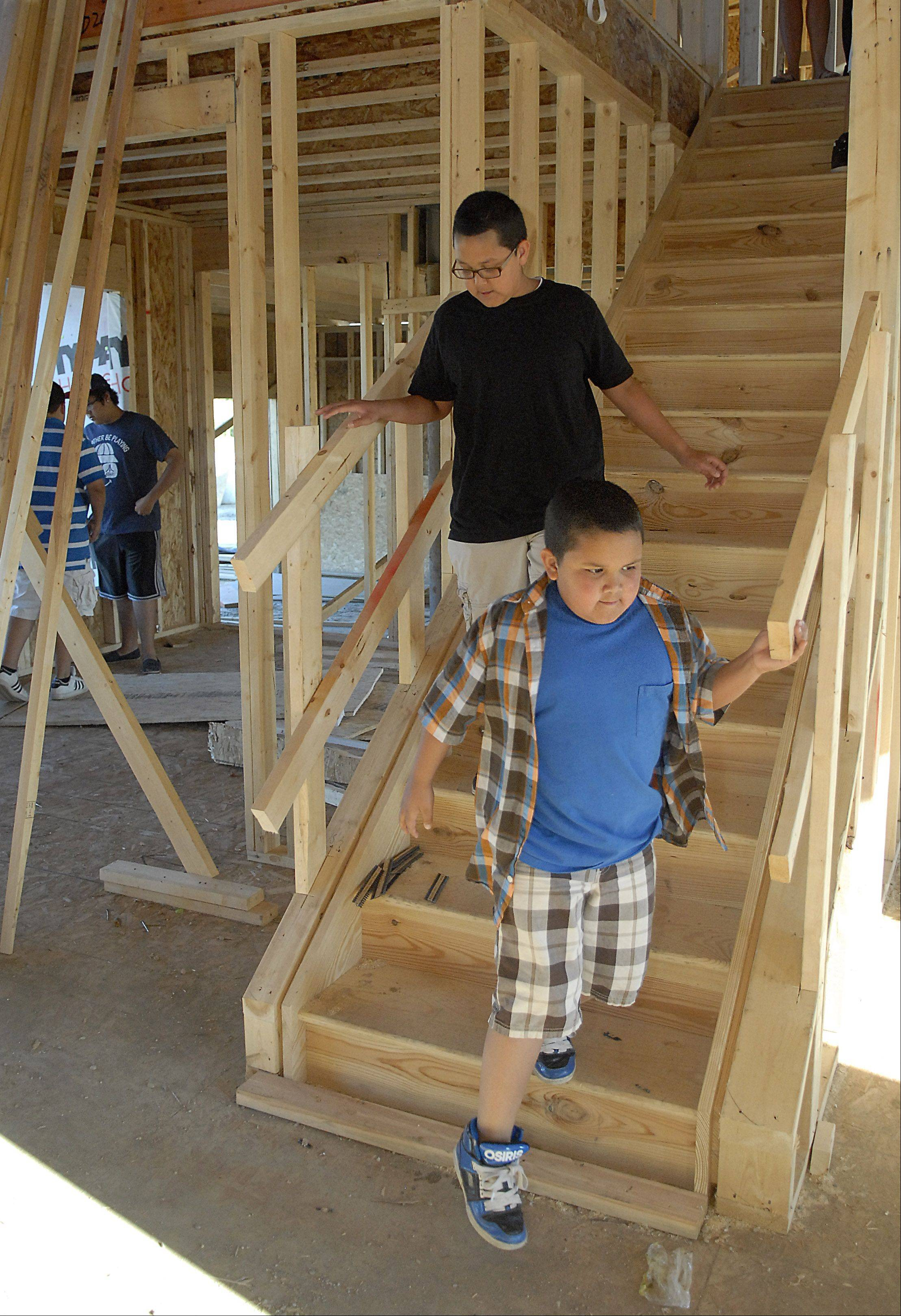 Stephen Lopez, 11, and brother Matthew, 7, investigate their new home being constructed. Michelle Lopez and her boyfriend, Peter Truschke, are having a home built in the Winchester Glen subdivision in Carpentersville. They expect it to be completed by August.